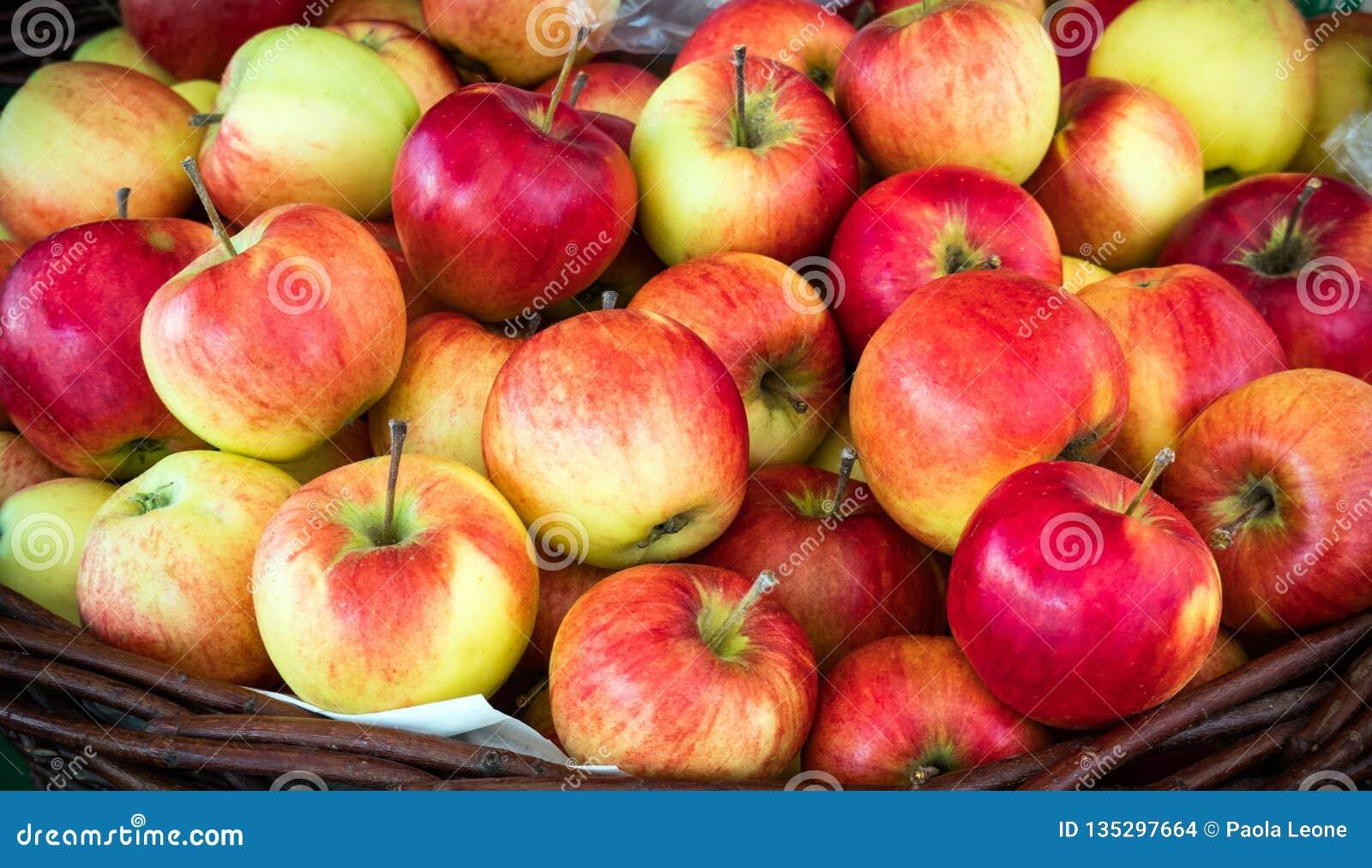 Le mele rosse succose fresche impilano in un canestro sulla vendita Bello sfondo naturale