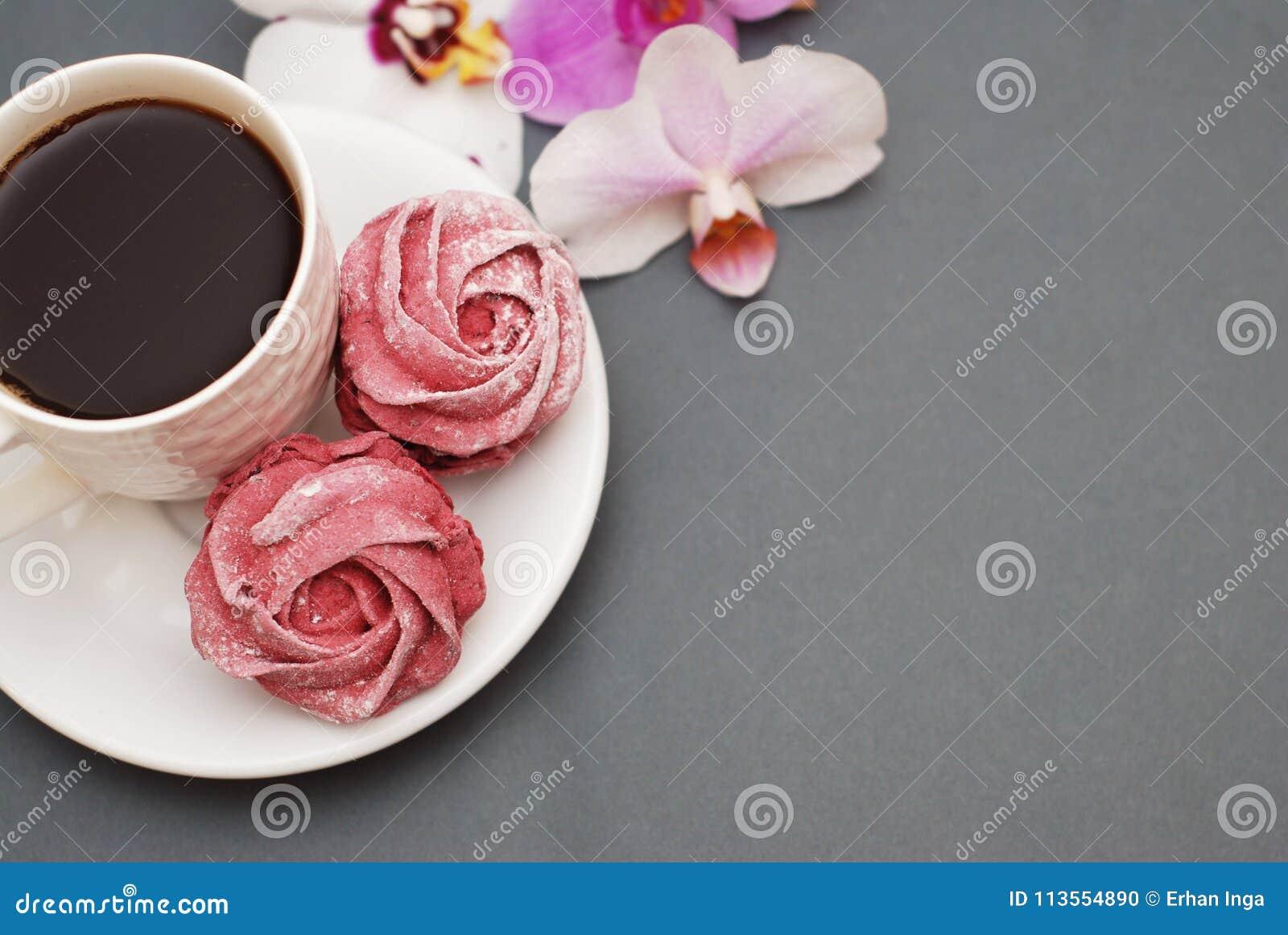 Le meringhe e la tazza di caffè rosa dolci sul fondo di Gray blu con l orchidea fiorisce Fondo della primavera con lo spazio dell