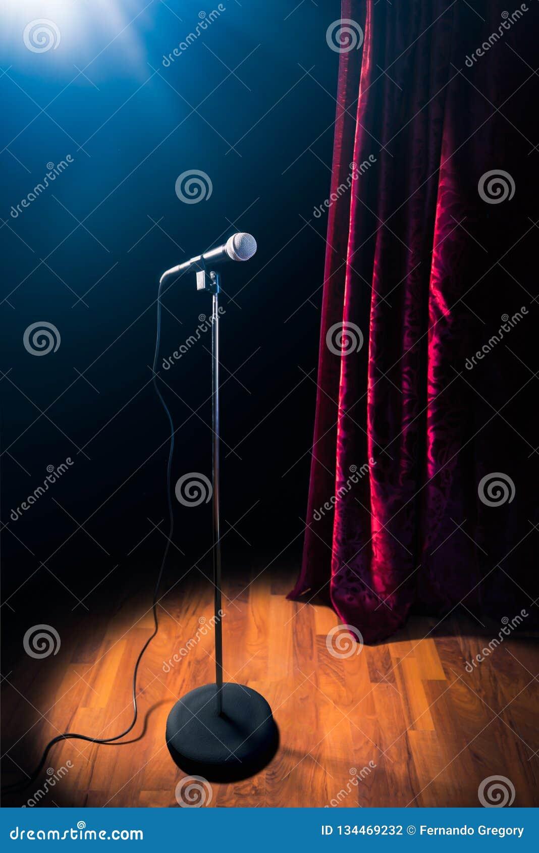 Le microphone sur une étape de comédie de support avec des réflecteurs rayonnent, image contrastée