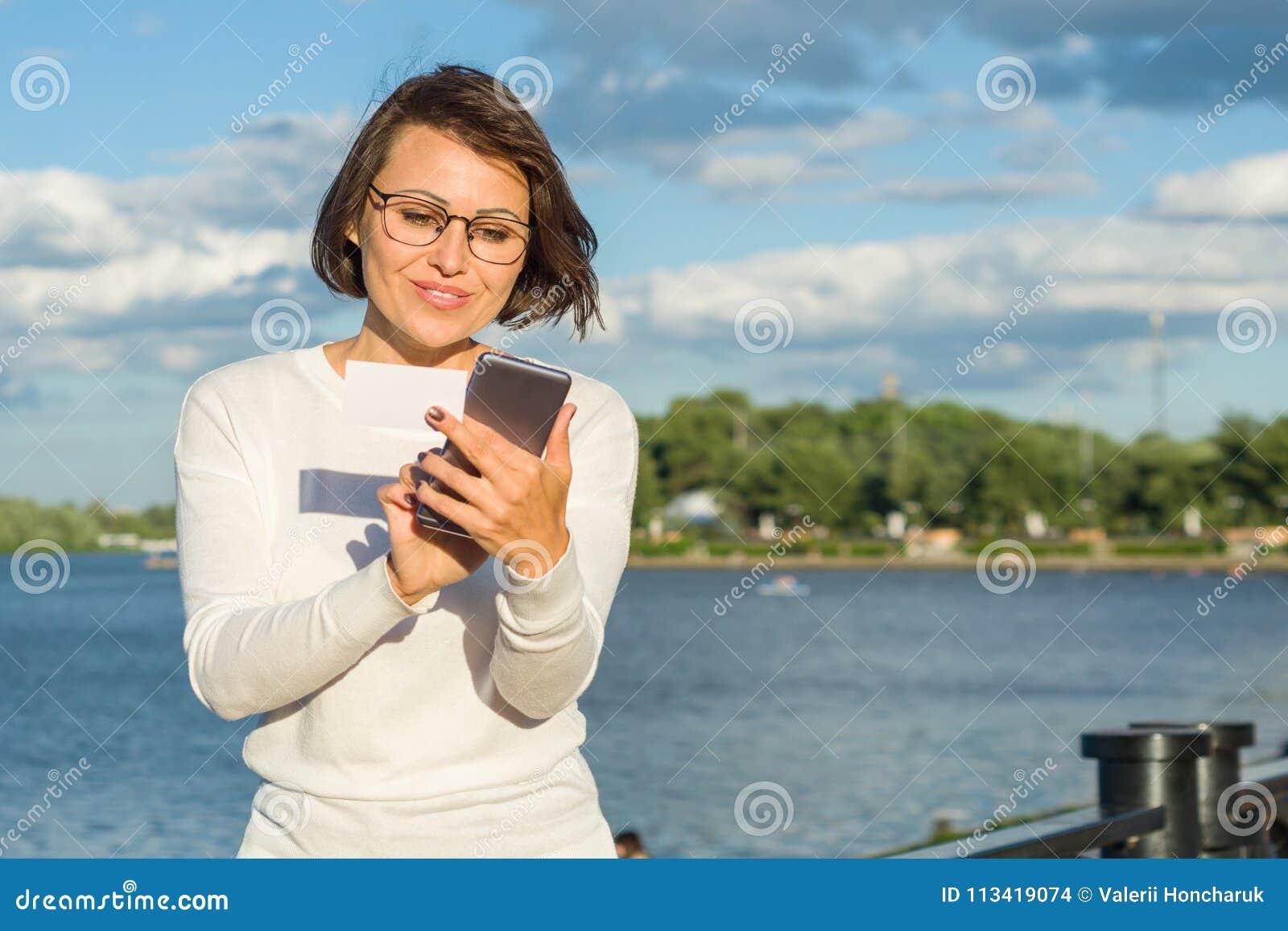 Le milieu heureux attrayant de portrait extérieur a vieilli le voyageur féminin de blogger d indépendante de femme avec le téléph
