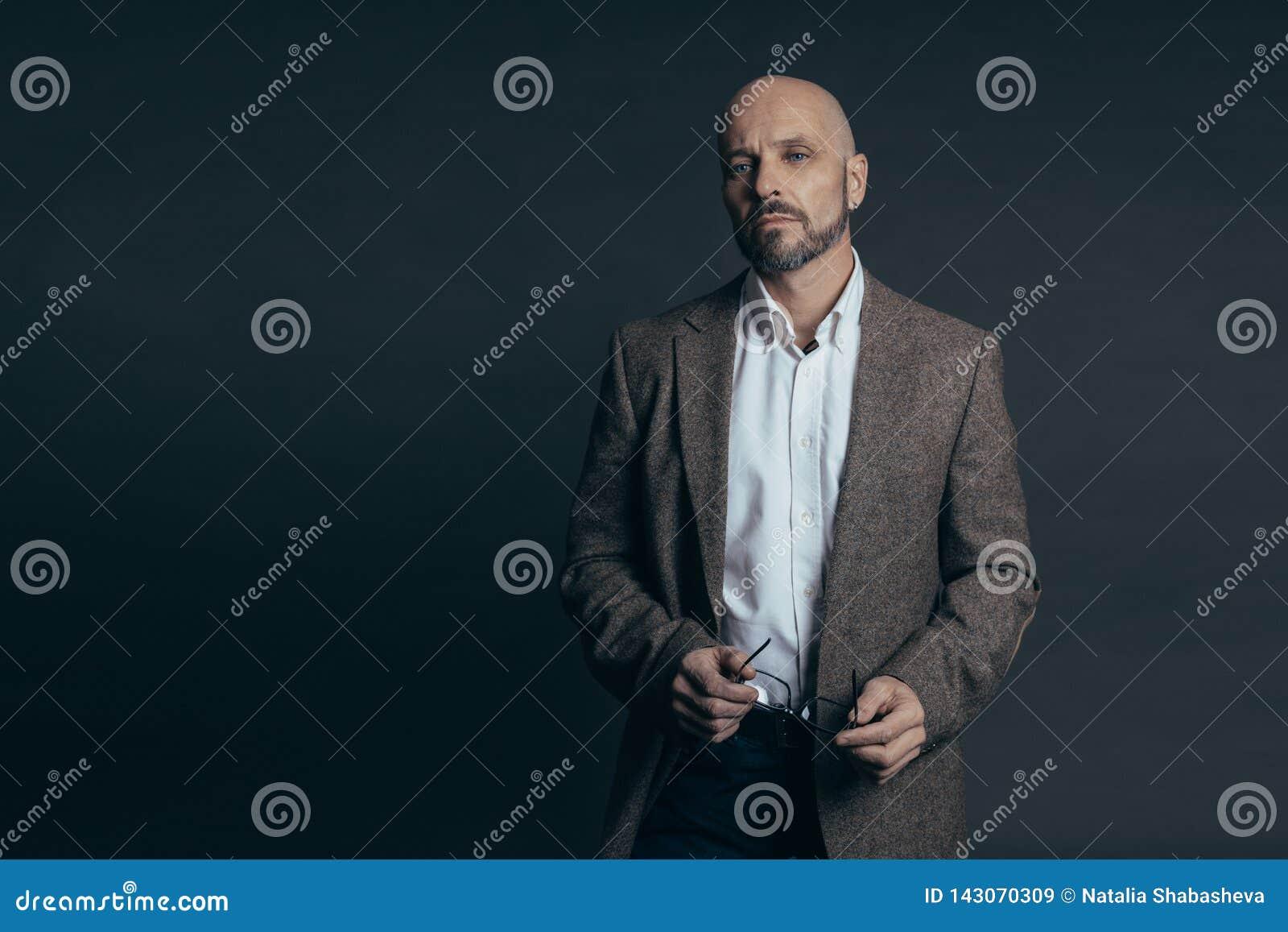 Le milieu sérieux a vieilli l homme avec une expression figée de visage habillé dans la pose occasionnelle sur un fond gris-foncé
