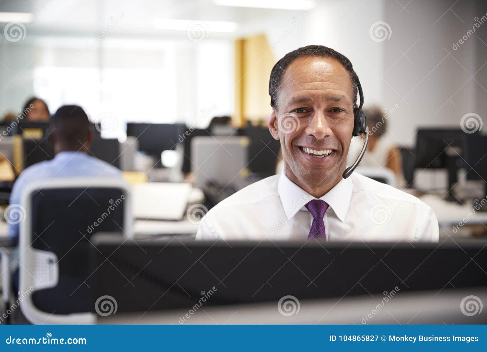 Le milieu a vieilli l homme travaillant à l ordinateur avec le casque dans le bureau
