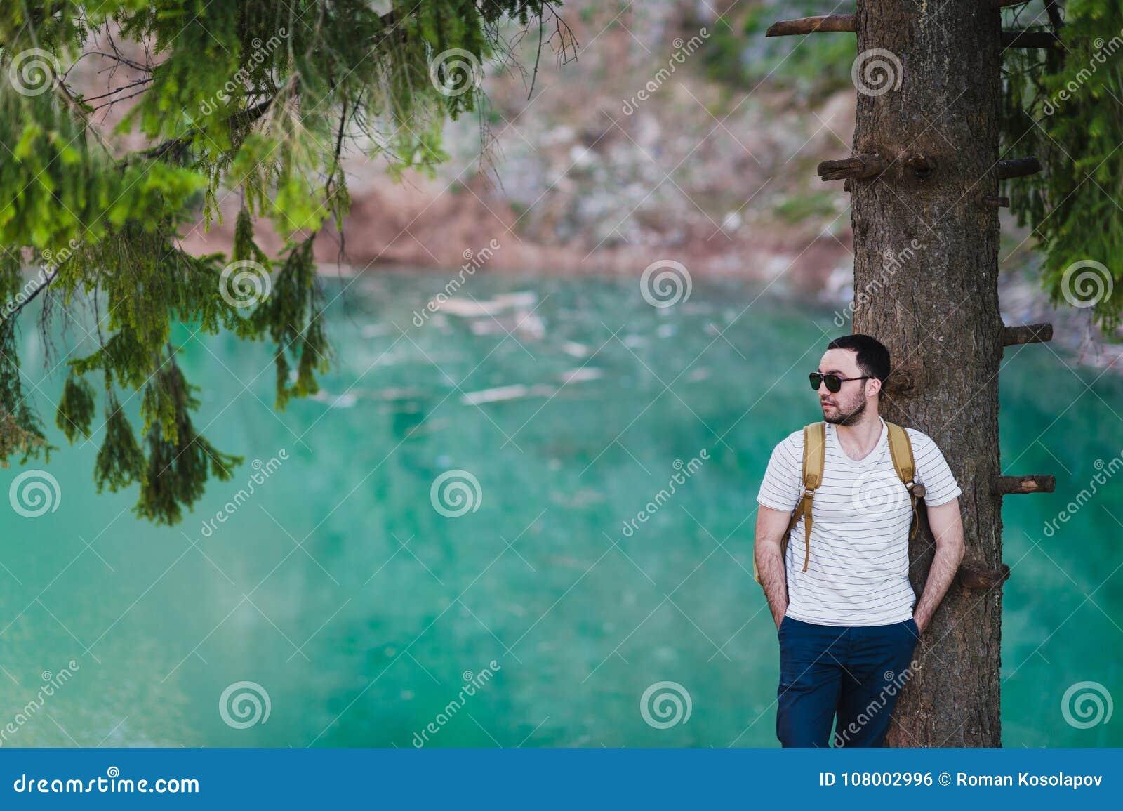 Le modèle barbu d homme pose à côté d un lac vert de l eau