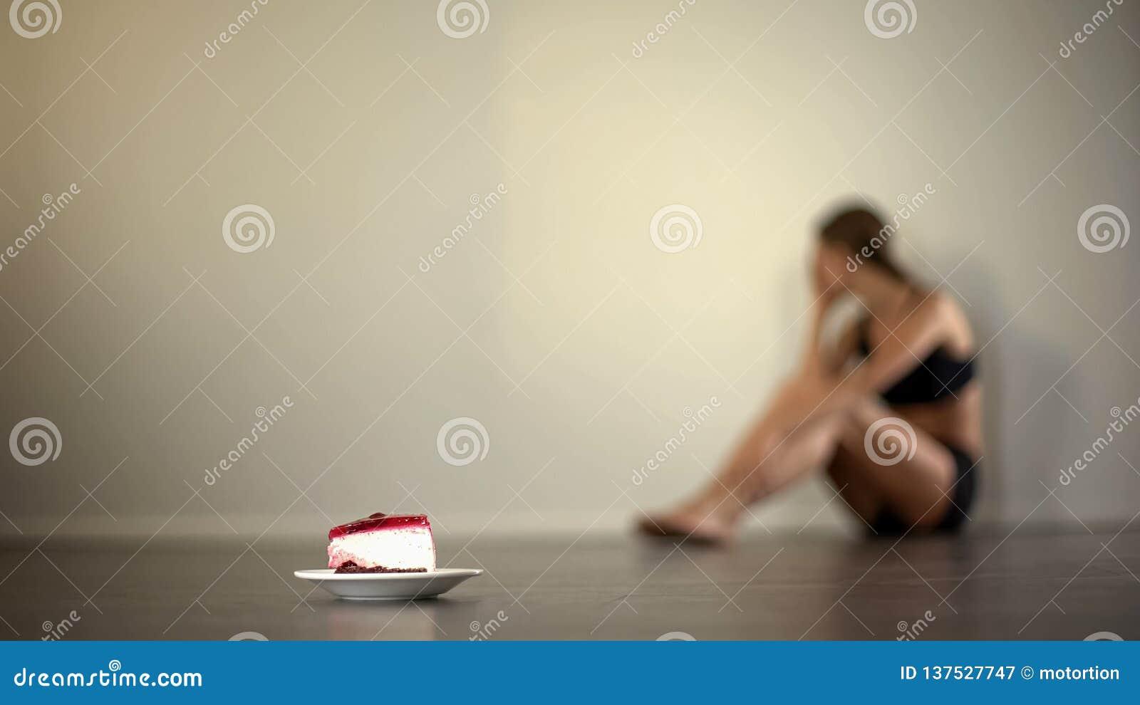 Le modèle maigre sent la nausée en regardant le gâteau, anorexie, trouble de la nutrition