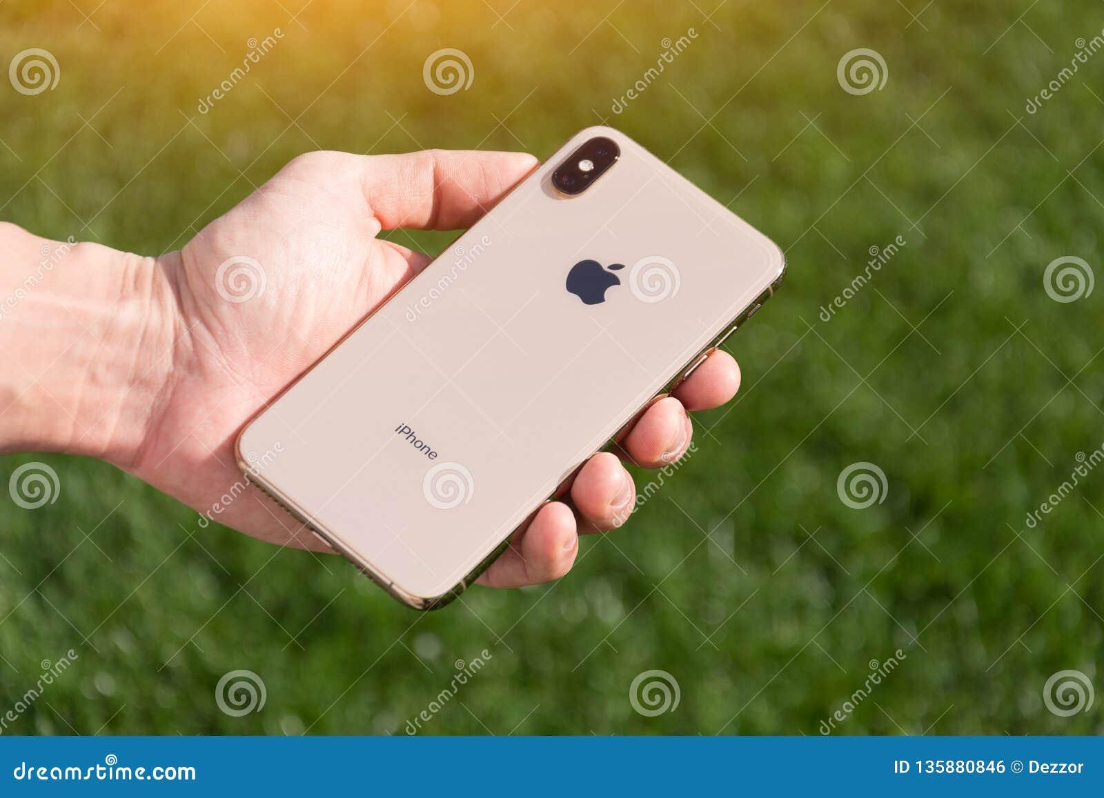 Le modèle maximum de smartphone d or d IPhone Xs par des ordinateurs Apple se ferment dans la main masculine sur le fond de l her