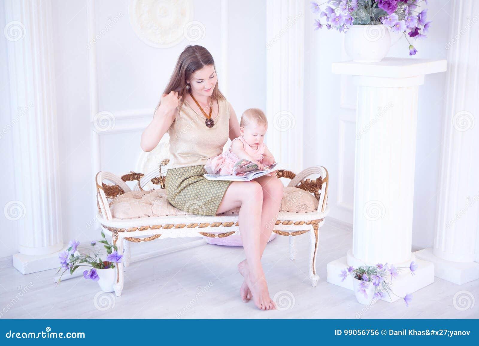 Le modern och hennes lilla dotter läs på en bok