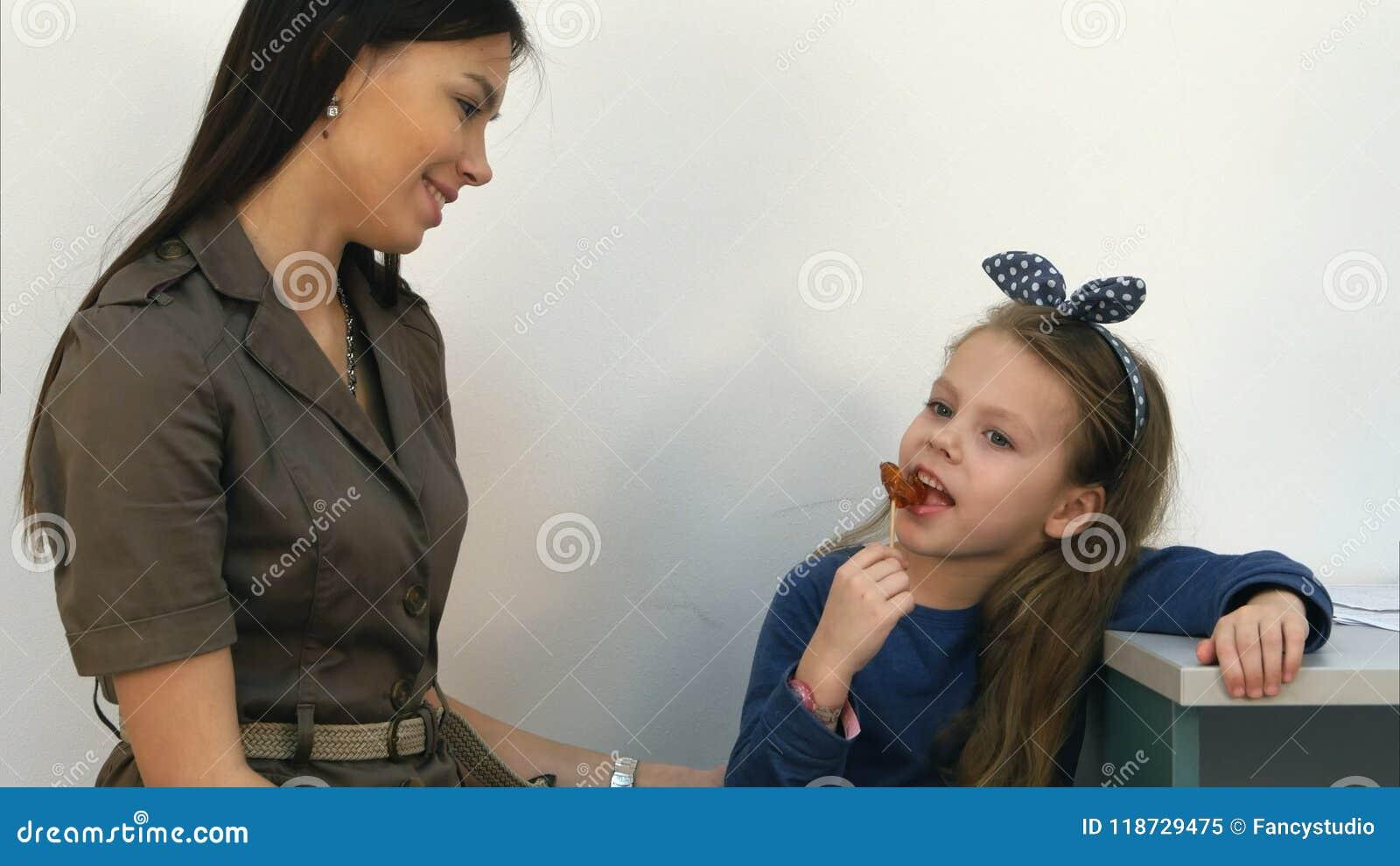Le modern som talar till hennes liten flicka som äter en klubba på kontoret för doktors` s