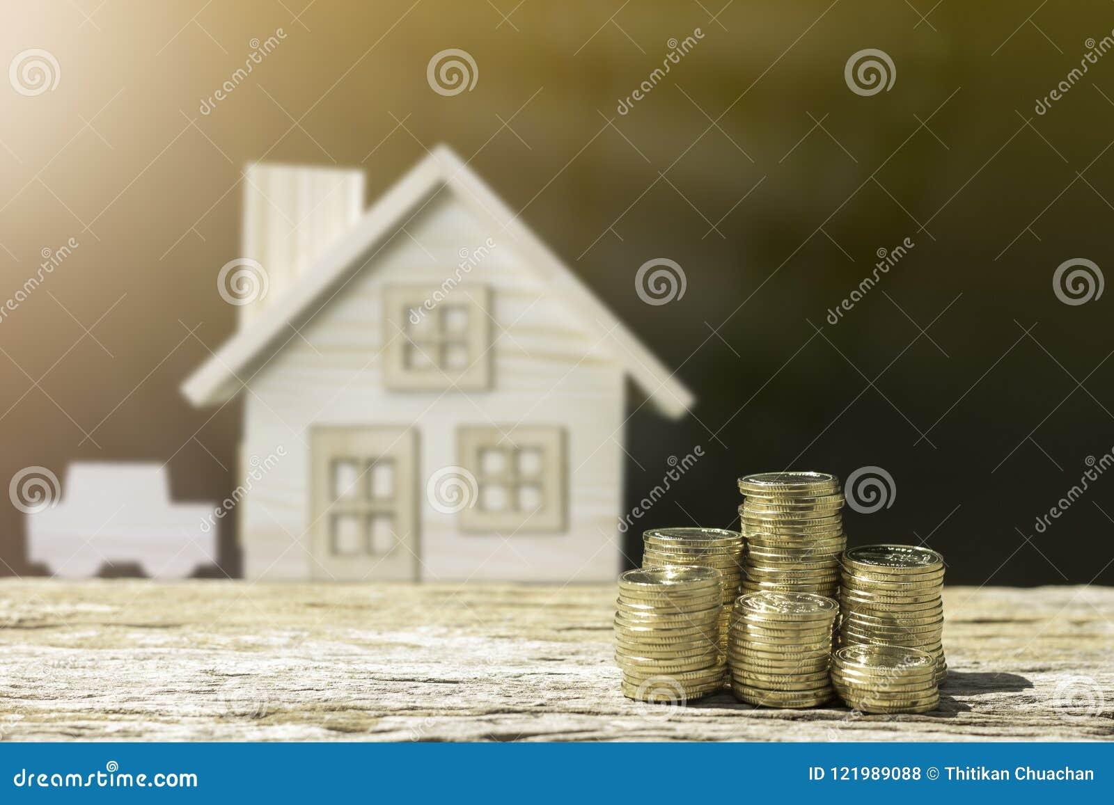 Le monete ed il fondo della sfuocatura della casa mostrano i soldi di risparmio