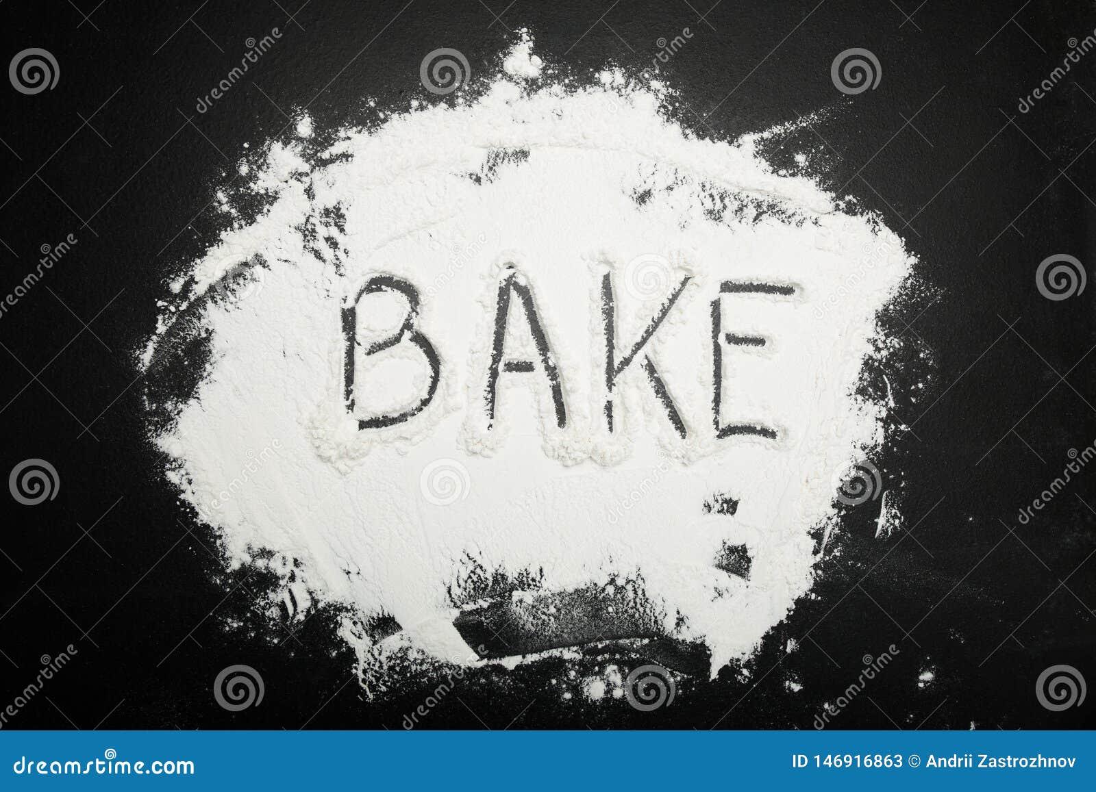 Le mot font cuire au four est écrit sur la farine sur un fond noir