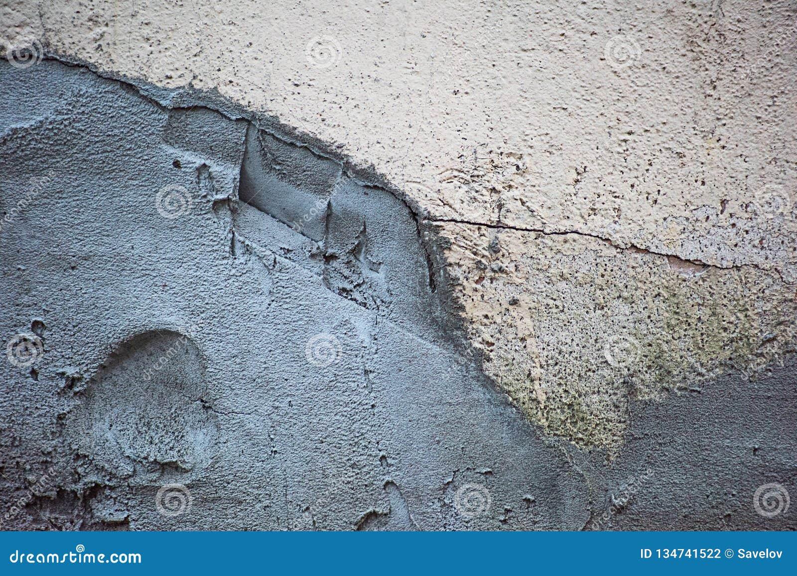 Le mur dans les fissures plâtrées avec le ciment