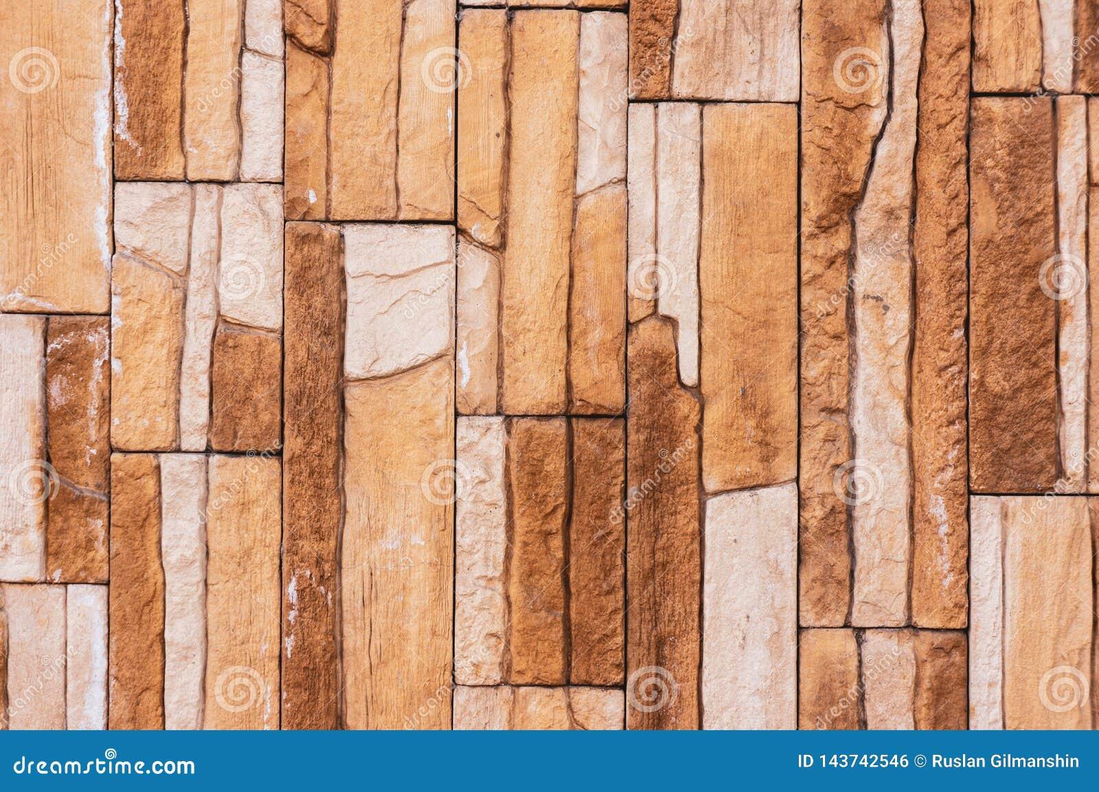 Le mur de tuile de brique de pierre de roche a une couleur brune crème de fond de sépia détaillée de texture empilé dans les couc