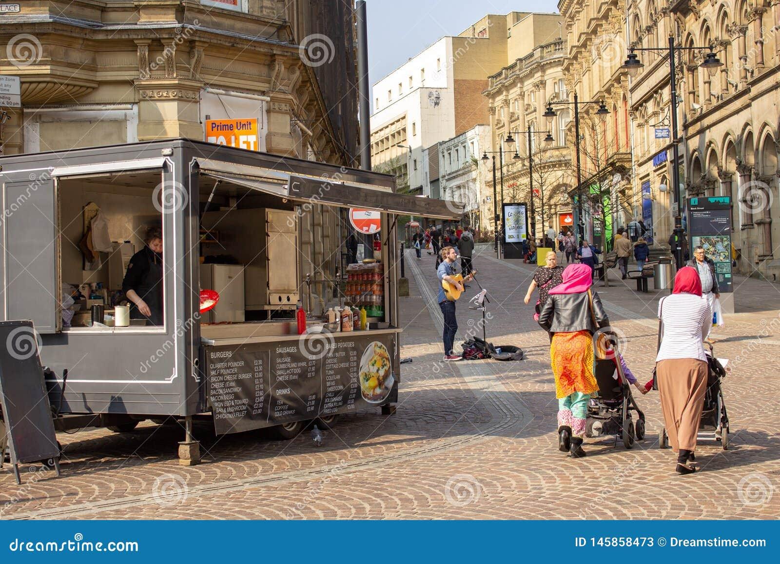 Le musicien de rue amuse des clients ? Bradford, Yorkshire