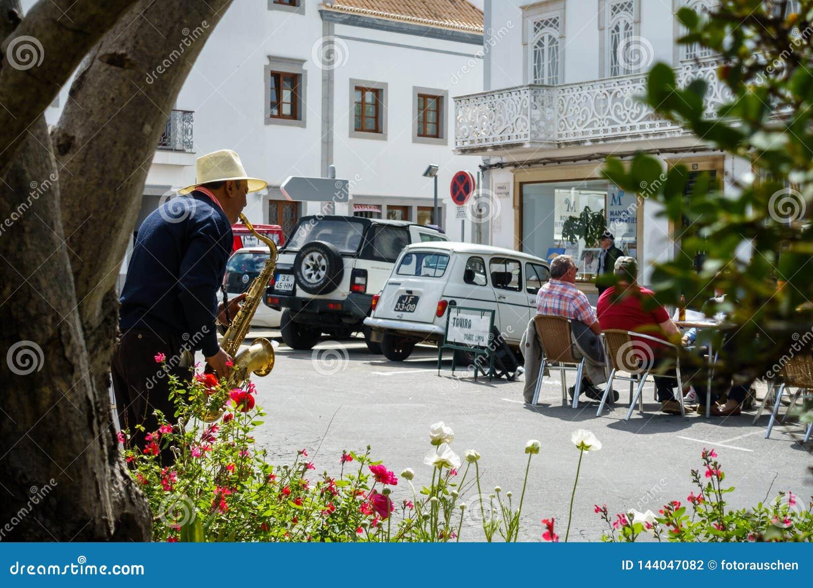 Le musicien de rue avec le chapeau joue la musique de jazz pour des touristes - scène de rue