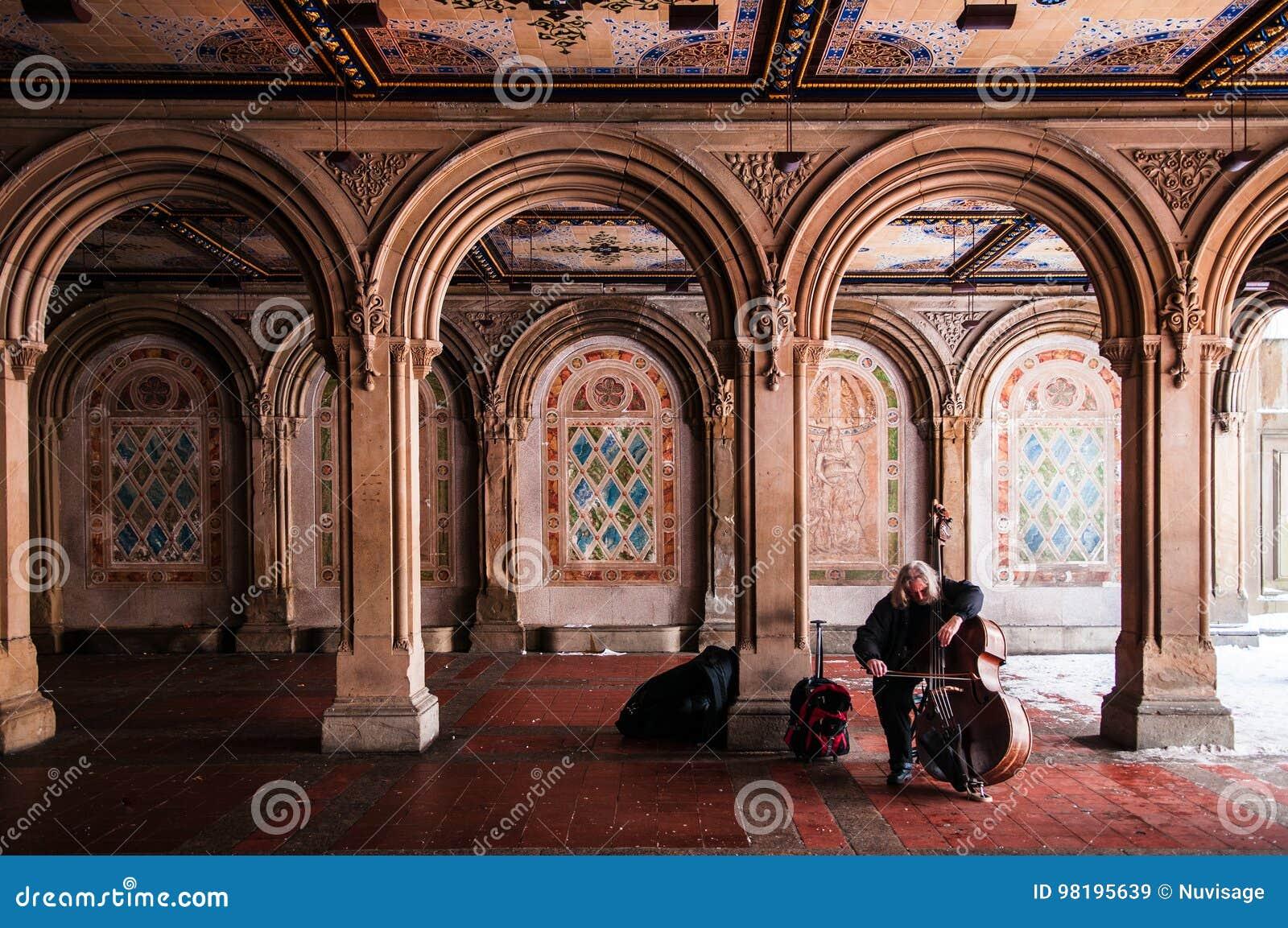 Le musicien de rue joue le violoncelle chez Bethesda Terrace, le Central Park, N