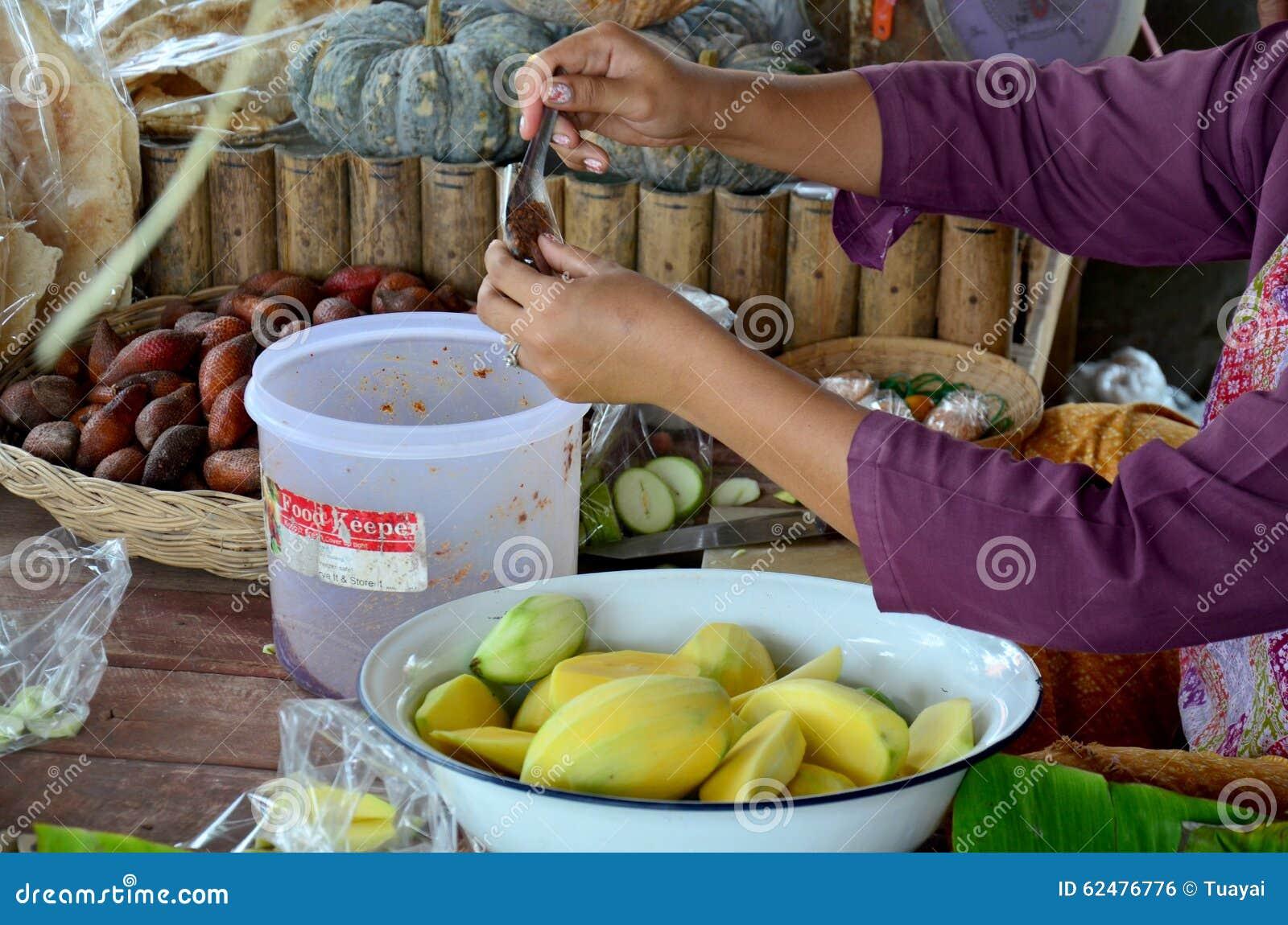 Le négociant thaïlandais préparent le piment avec du sel et la sauce au poivre pour la mangue