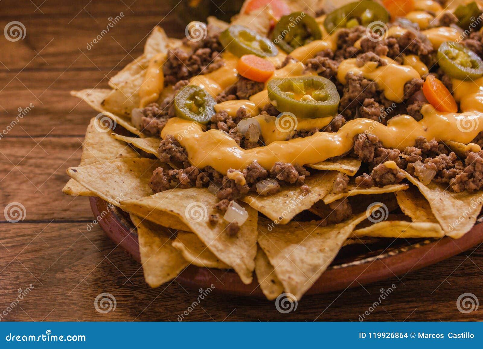 Le Nacho ébrèche le maïs garni avec le boeuf haché, fromage fondu, les poivrons de jalapeño, nourriture épicée mexicaine au Mexi