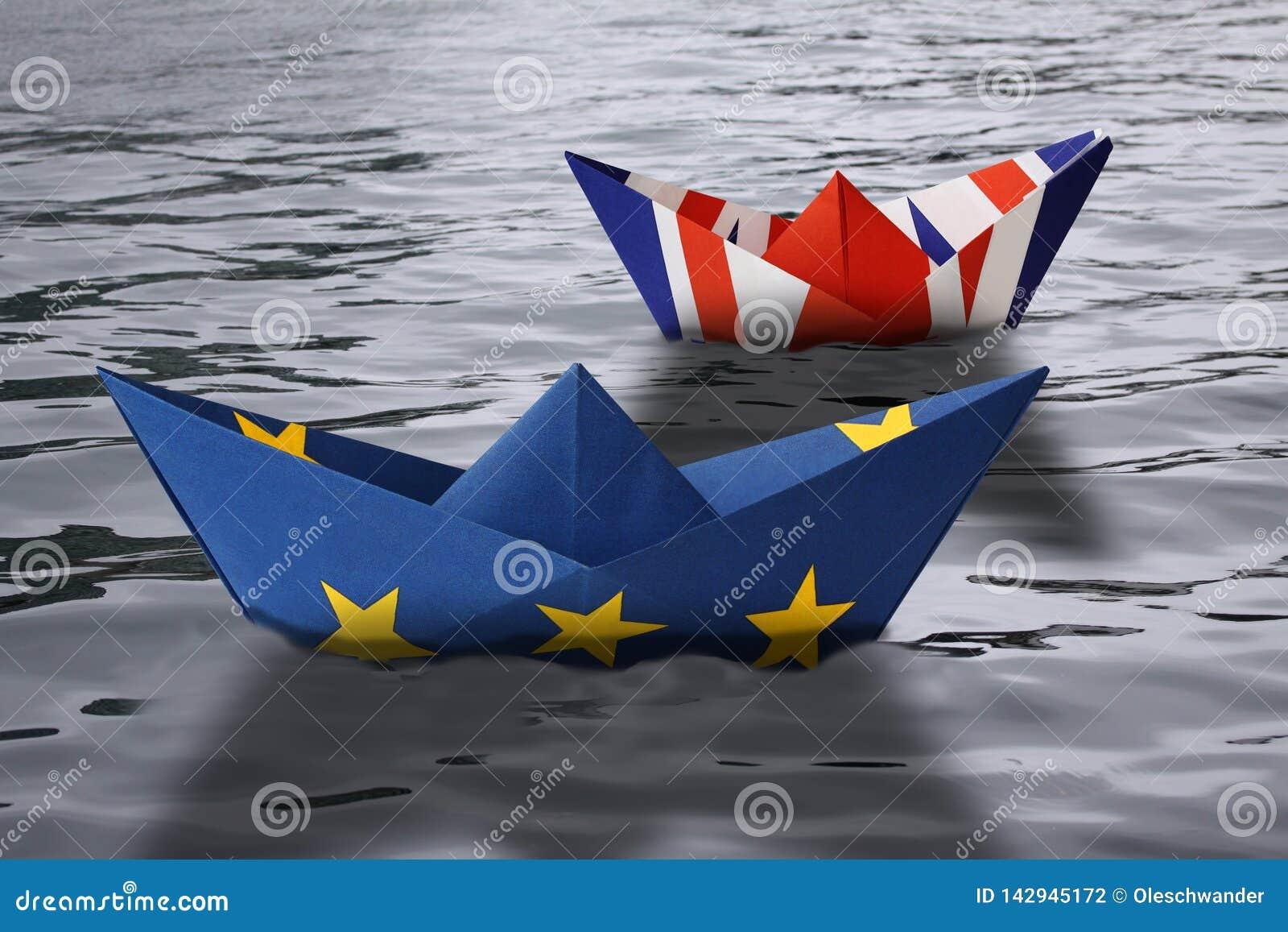 Le navi di carta hanno fatto come Unione Europea e bandiere britanniche che navigano parallelamente nella rappresentazione acqua