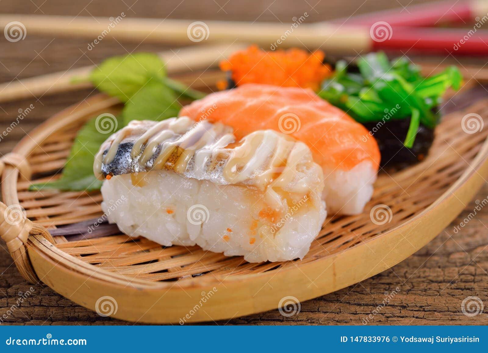 Le nigiri et le sashimi figés de sushi ont servi dans le plat en bambou sur le fond en bois