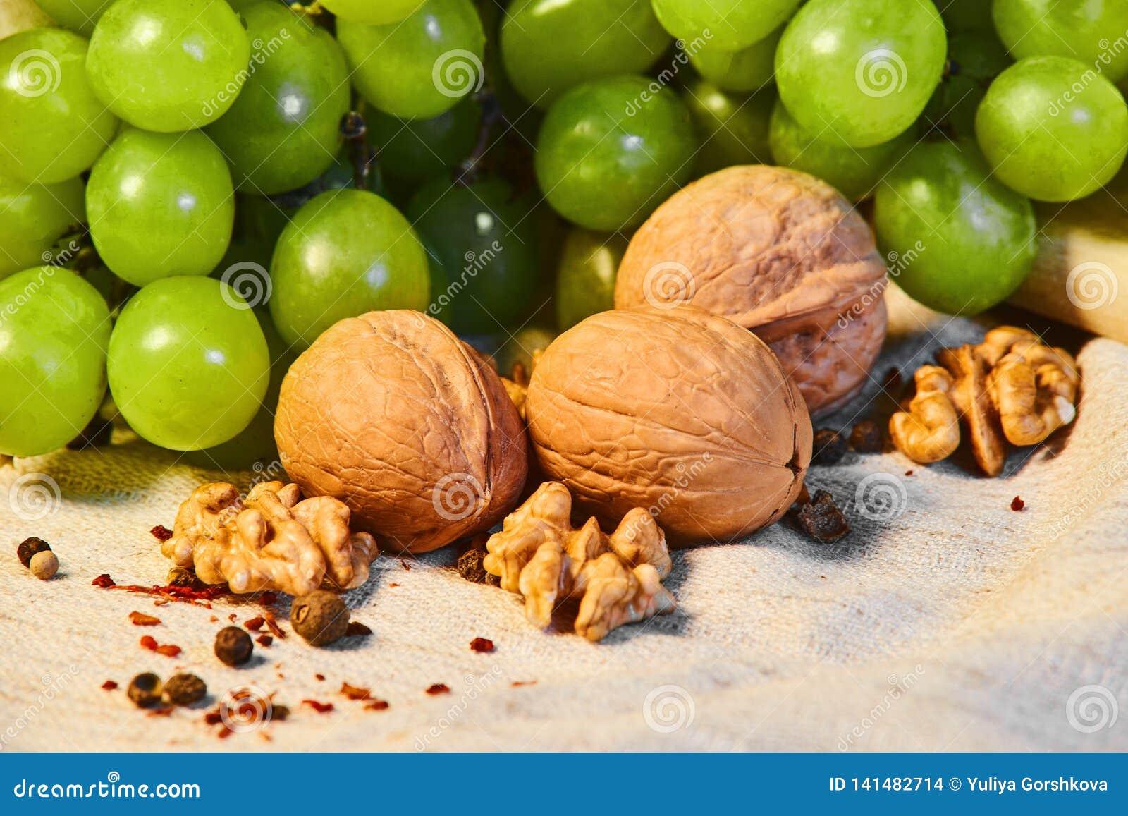 Le noci e l uva verde si trovano sul panno di tela con le spezie