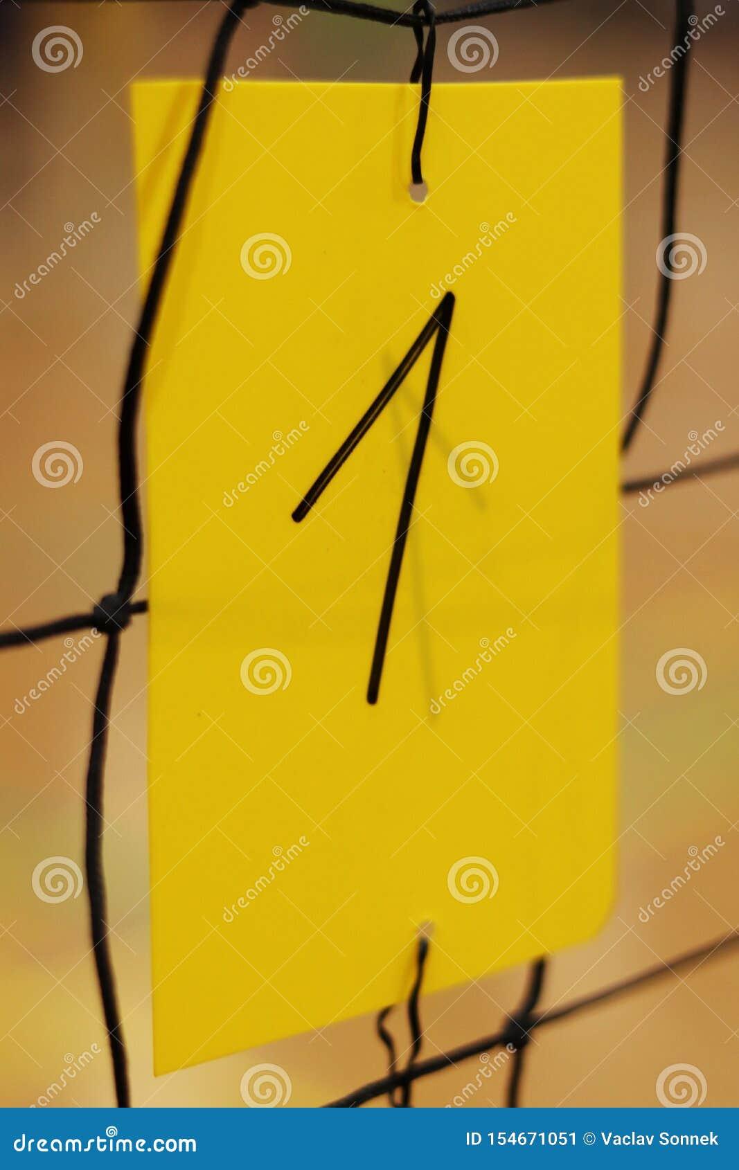 Le numéro un écrit par le marqueur noir sur la carte en plastique jaune se tient sur le filet de volleyball Nombre employé pour i