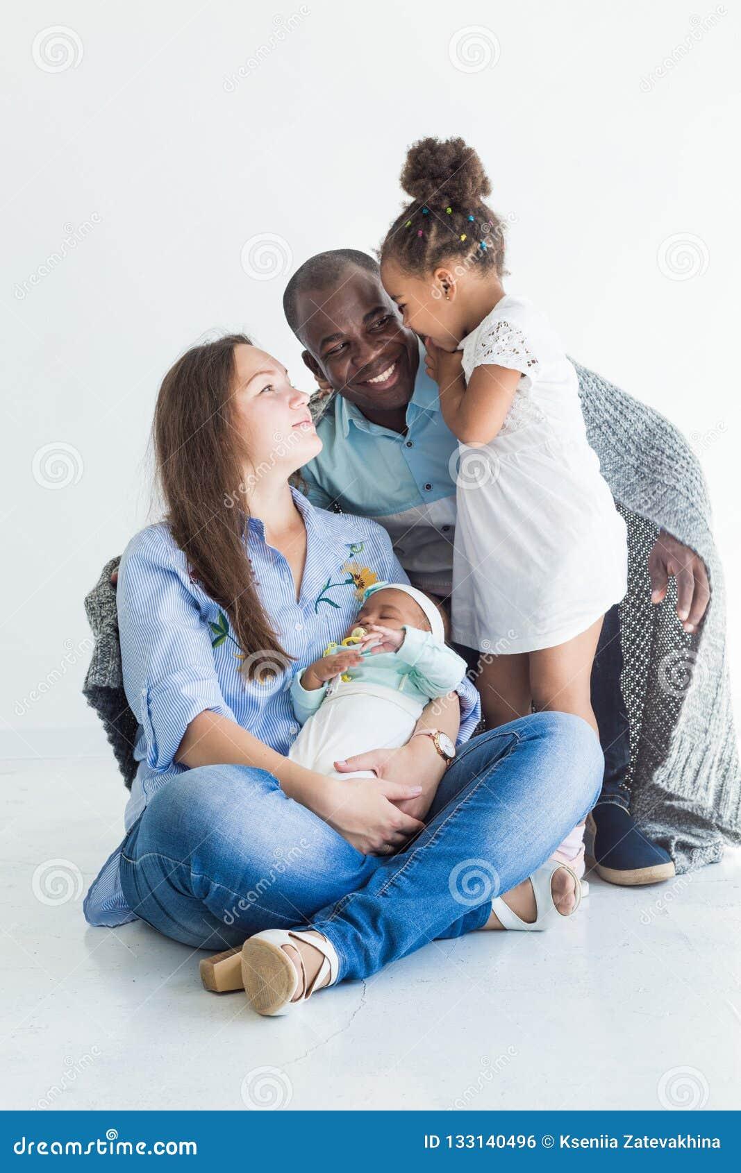 Le père aimant couvre sa famille de plaid Famille multi-ethnique heureuse Valeurs familiales