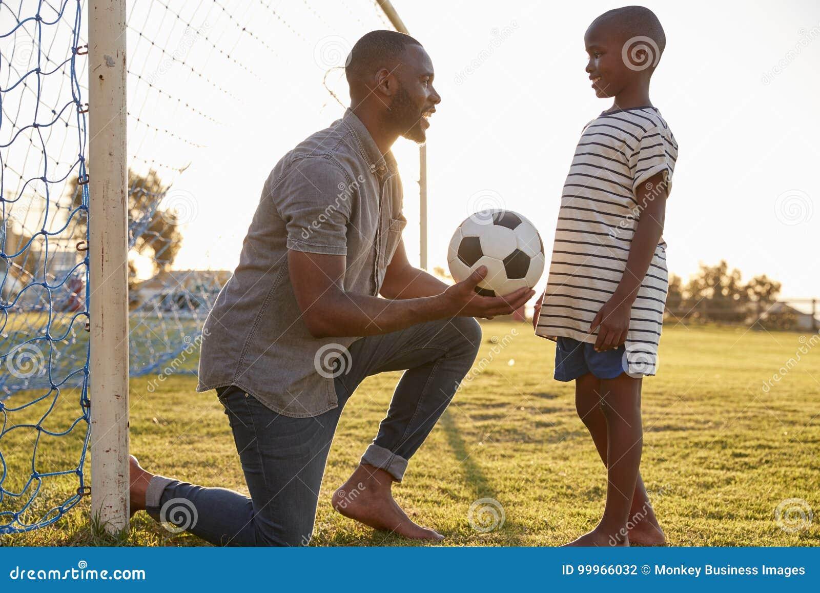Le père donne une boule à son fils pendant une partie de football