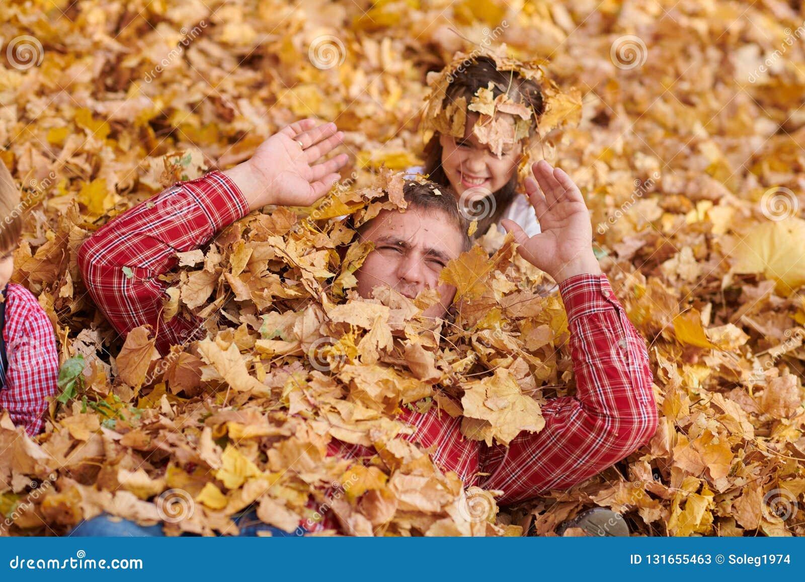 Le père et la fille se trouvent sur les feuilles jaunes et ont l amusement en parc de ville d automne Ils posant, sourire, jouant