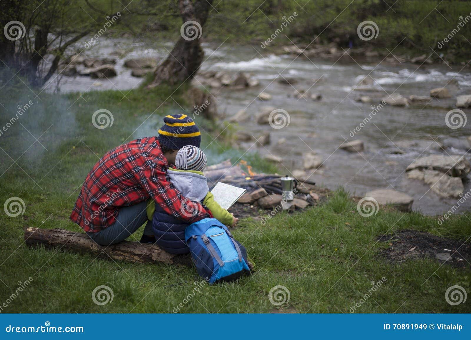 Le père et le fils s asseyant près d un feu de camp au terrain de camping et sont l