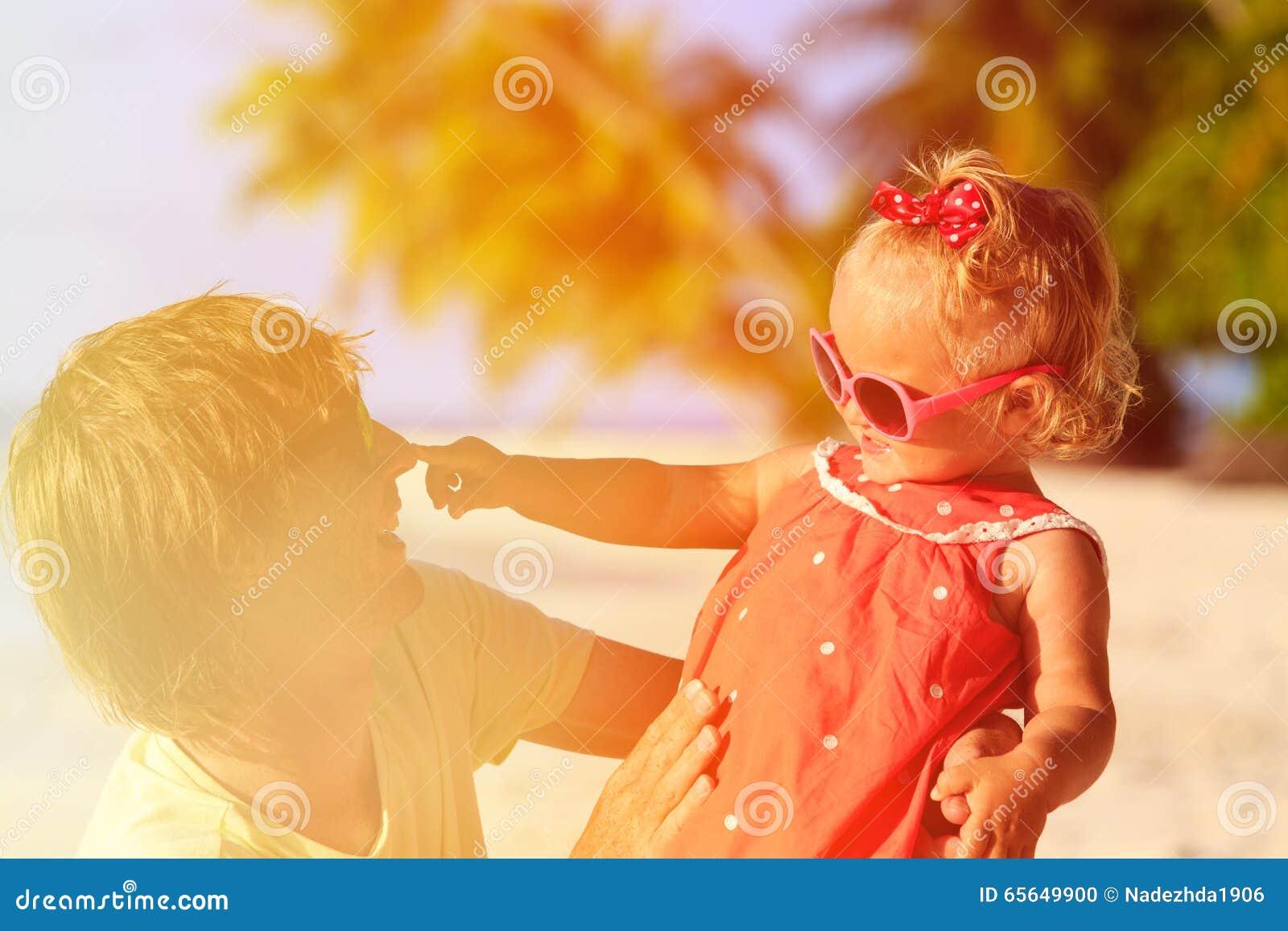 Le père heureux et la petite fille mignonne jouent à la plage