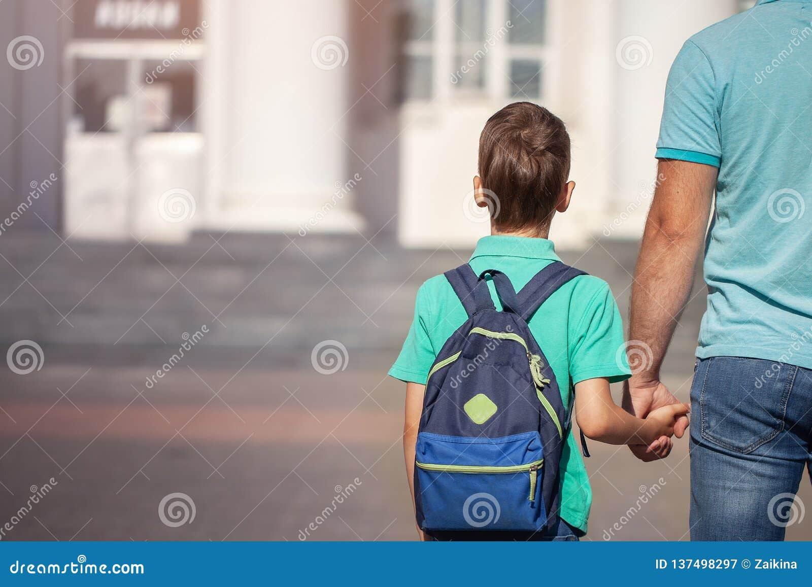 Le père mène un petit enfant que l écolier vont main dans la main Parent et fils avec le sac à dos derrière le dos