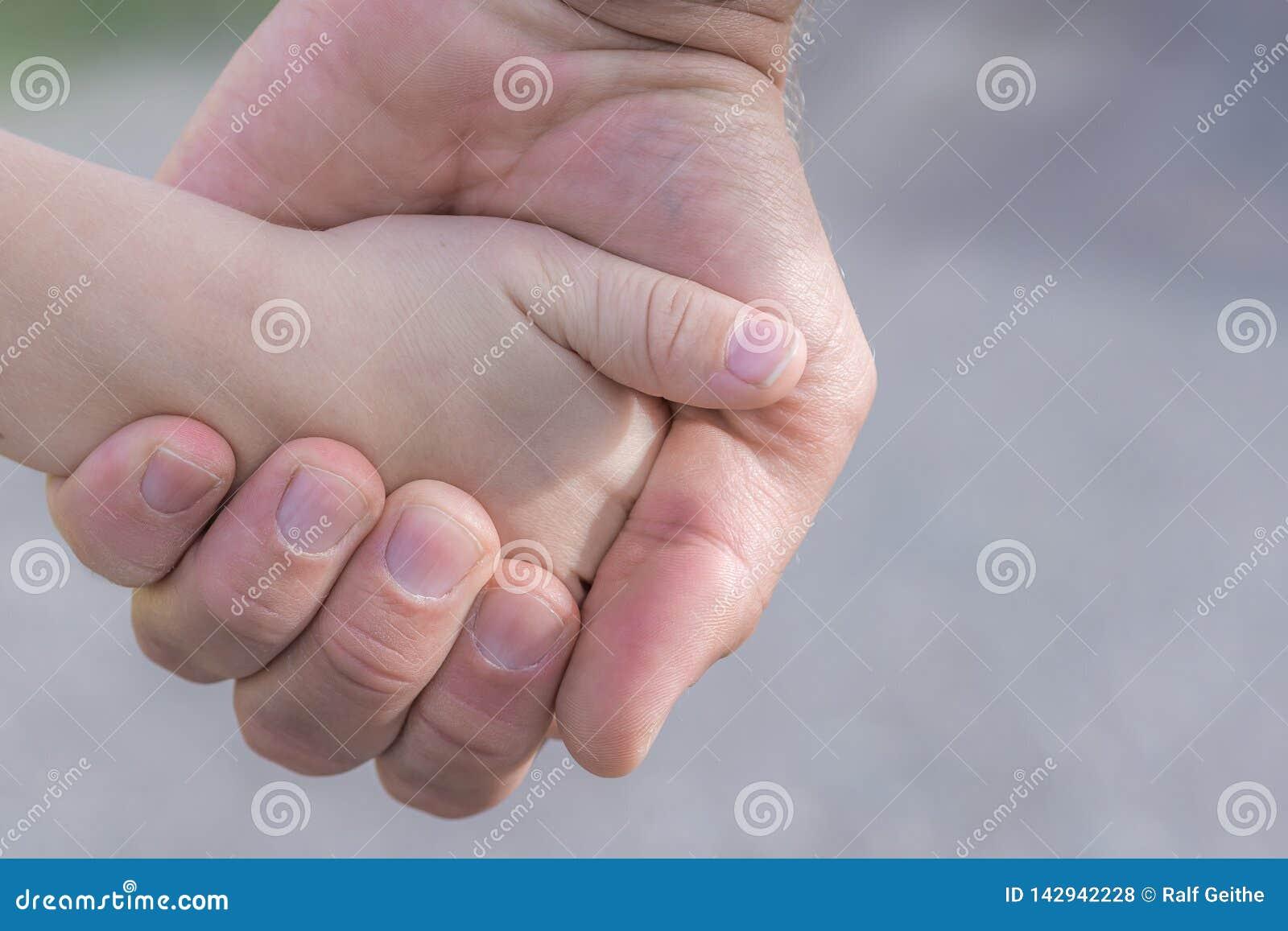 Le père tient la main de son enfant