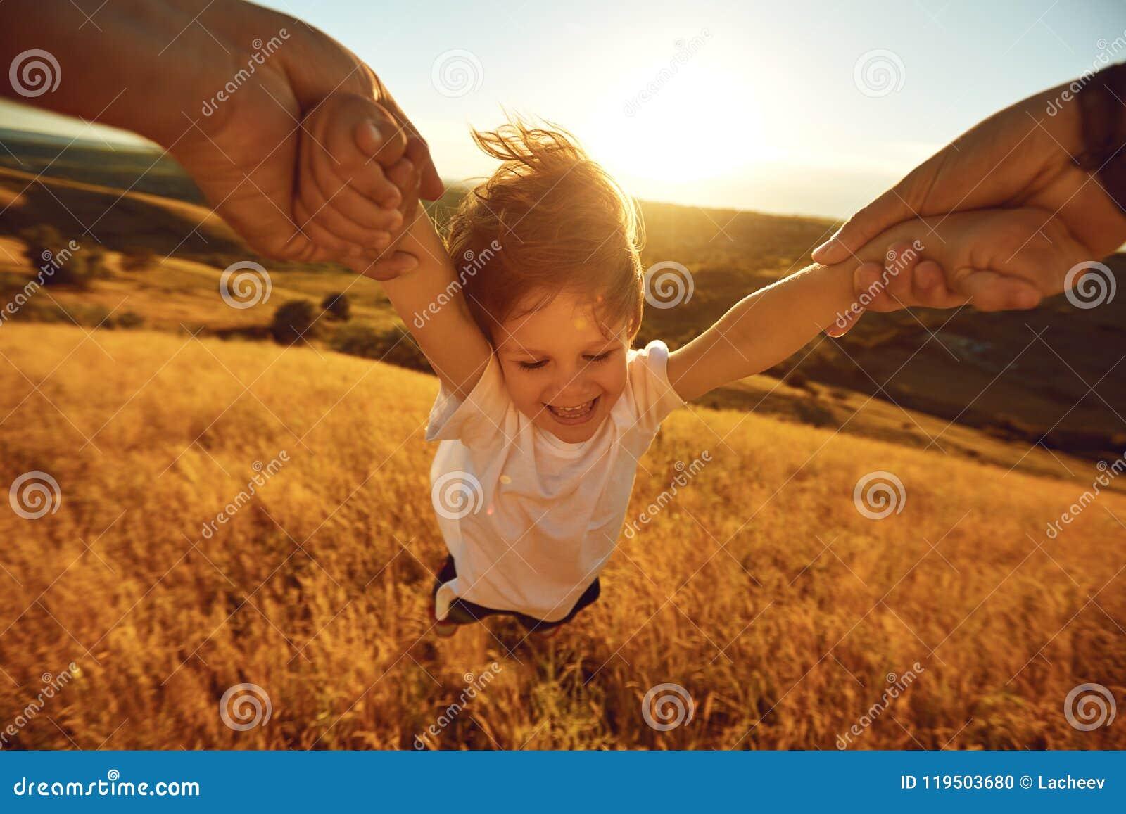Le père tourne un enfant dans le domaine en nature