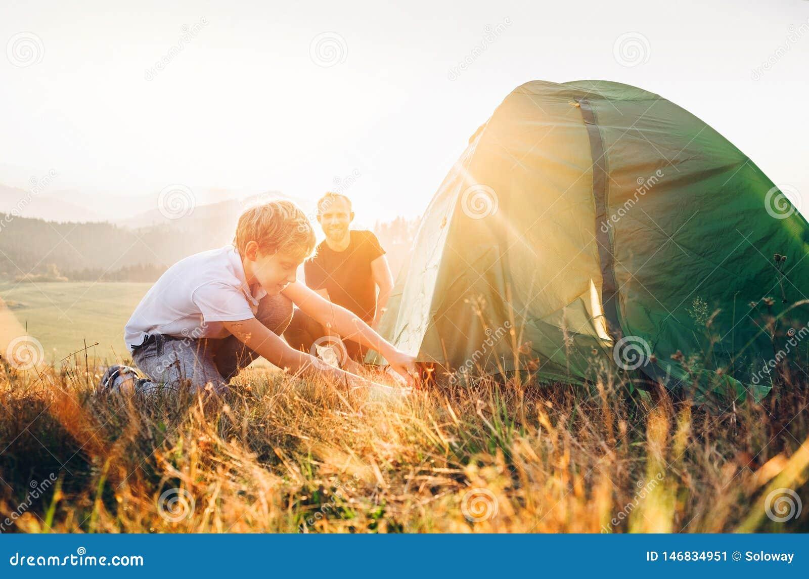 Le p?re apprennent sa tente de camping d installation de fils sur la clairi?re de for?t de coucher du soleil