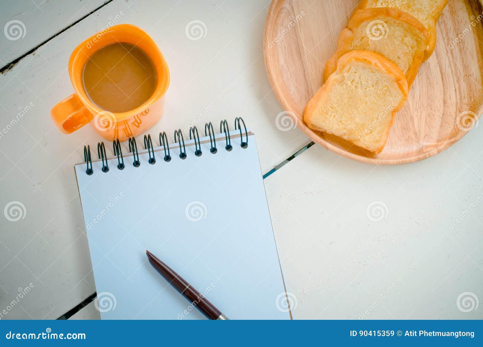 Le pain, café, le carnet, crayon sur le concept de bureau font une pause - la vie toujours
