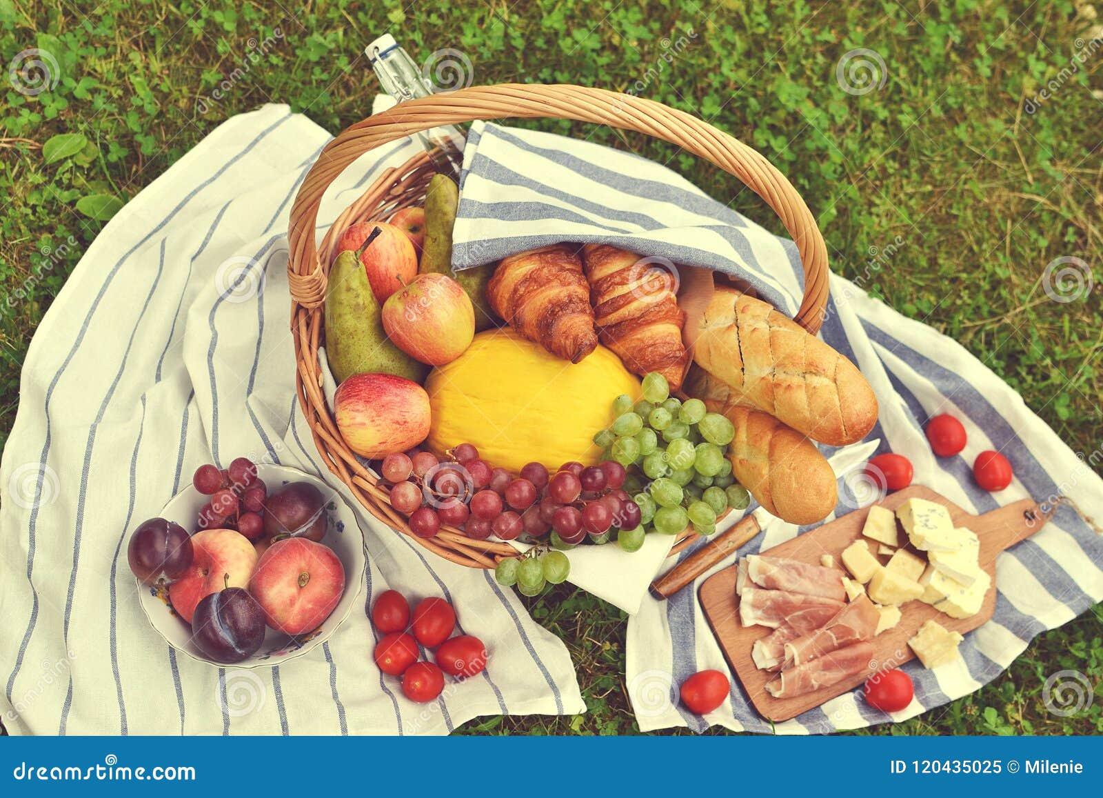 Le panier avec du fromage Ham Tomato Picnic Green Grass de boulangerie de fruit de nourriture a modifié la tonalité la photo