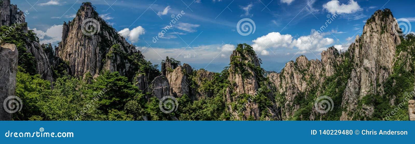 Le panorama des crêtes rocheuses et les vieux pins couvrent les montagnes sous un ciel bleu lumineux de nuages whispy à Huangshan