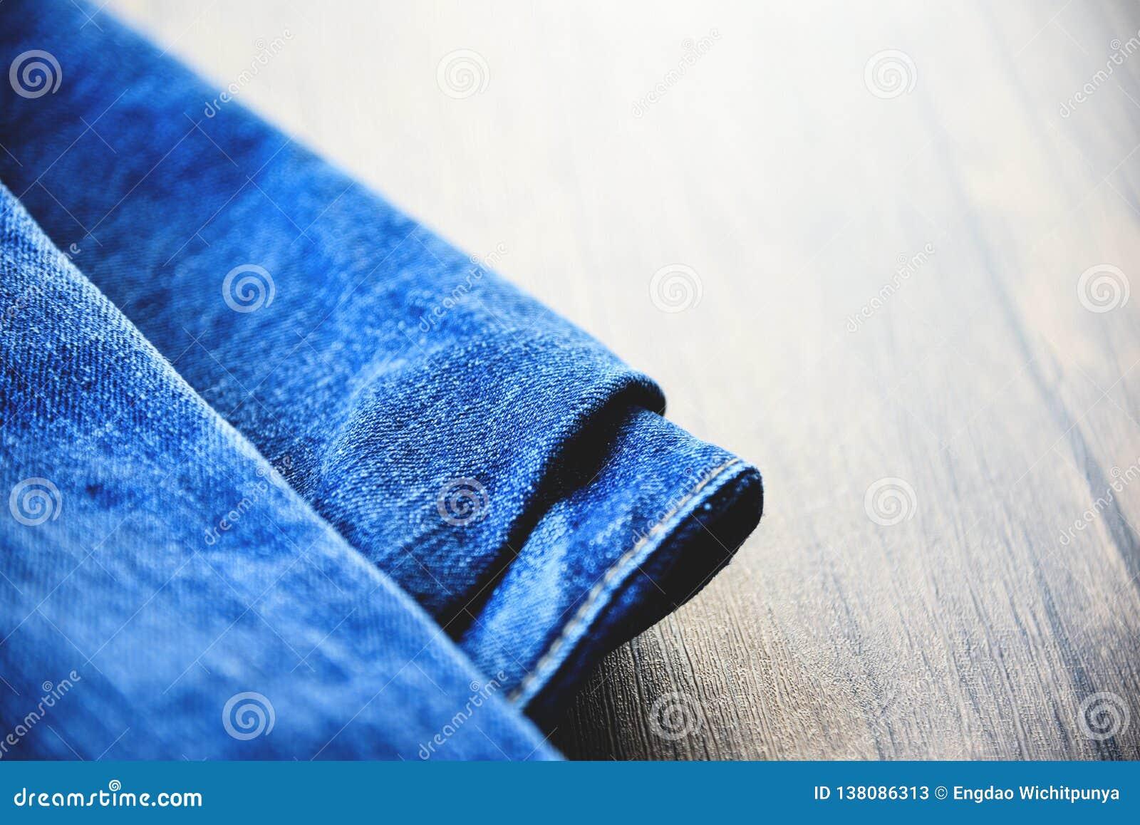 Le pantalon a plié le tissu de modèle de jeans utilisé des blues-jean sur le fond en bois
