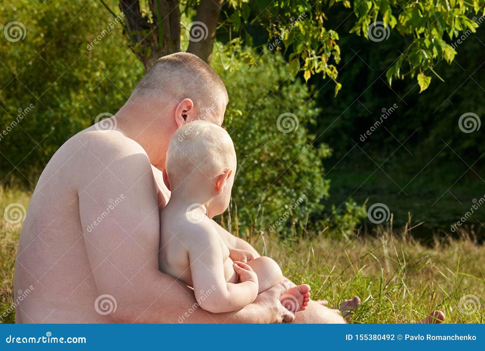 Le papa étreint son peu de fils sur les banques de la rivière un jour chaud d été Vue de c?t?