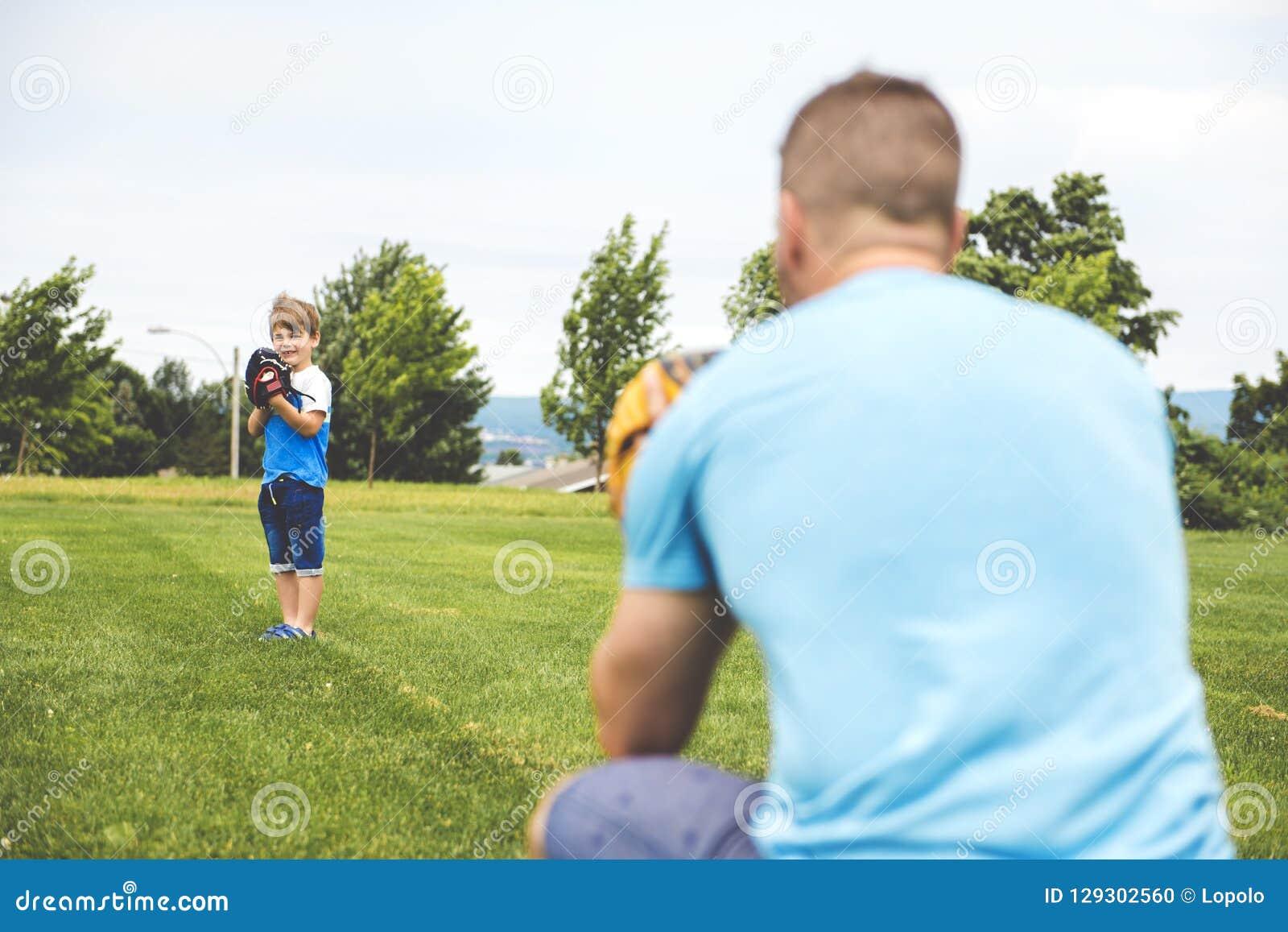 Le papa beau avec son petit soleil mignon jouent le base-ball sur la pelouse herbeuse verte