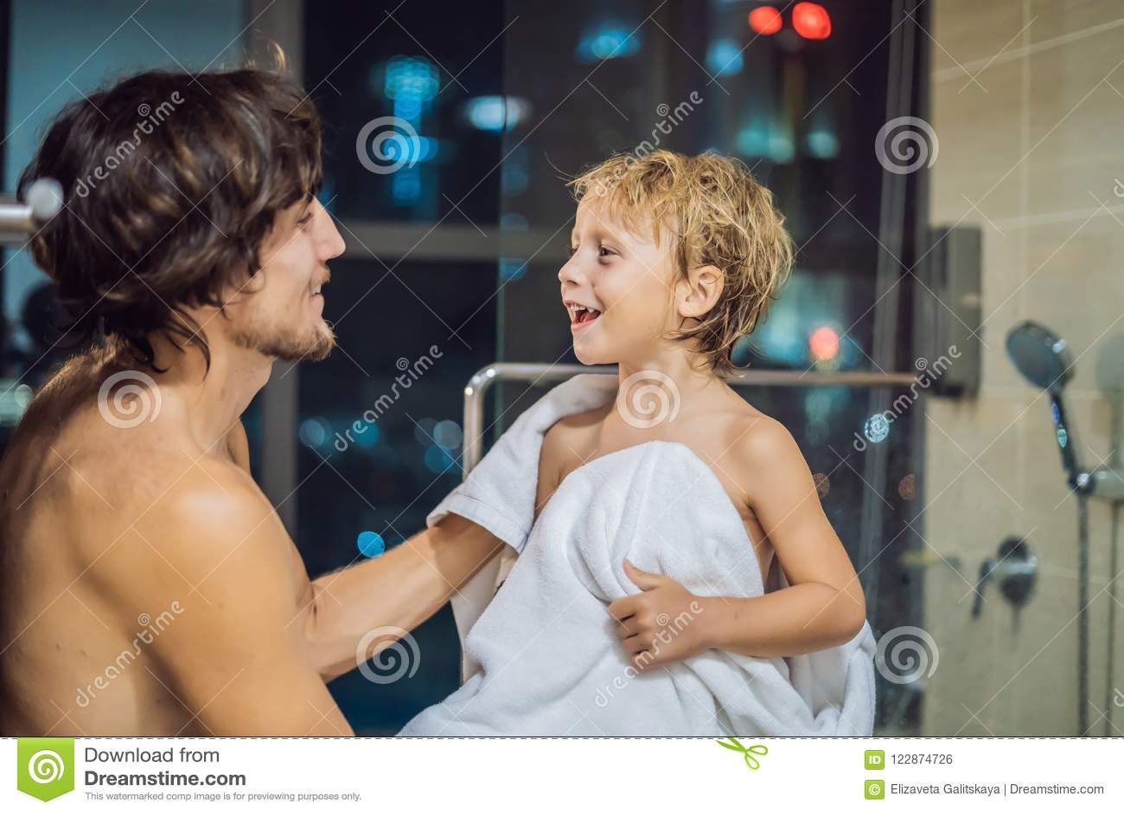 Le papa essuie son fils avec une serviette après une douche le soir avant d aller dormir sur le fond d une fenêtre avec un panora