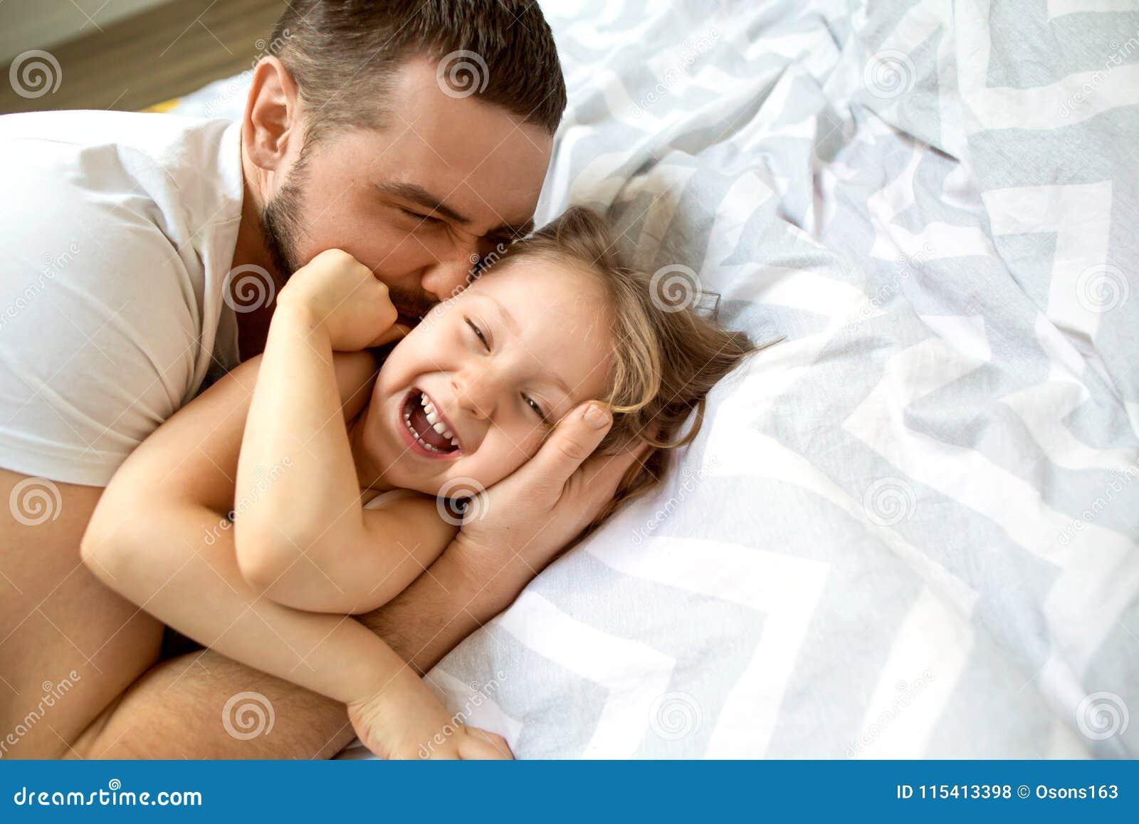 Le papa et la fille ont l amusement à la maison sur le lit Jour du `s de père