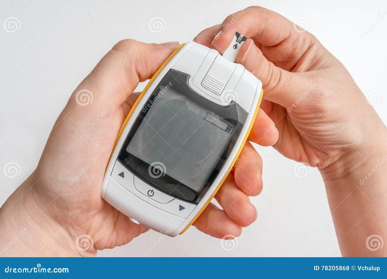 Le patient diabétique emploie le glucometer pour le niveau de mesure de glucose sanguin