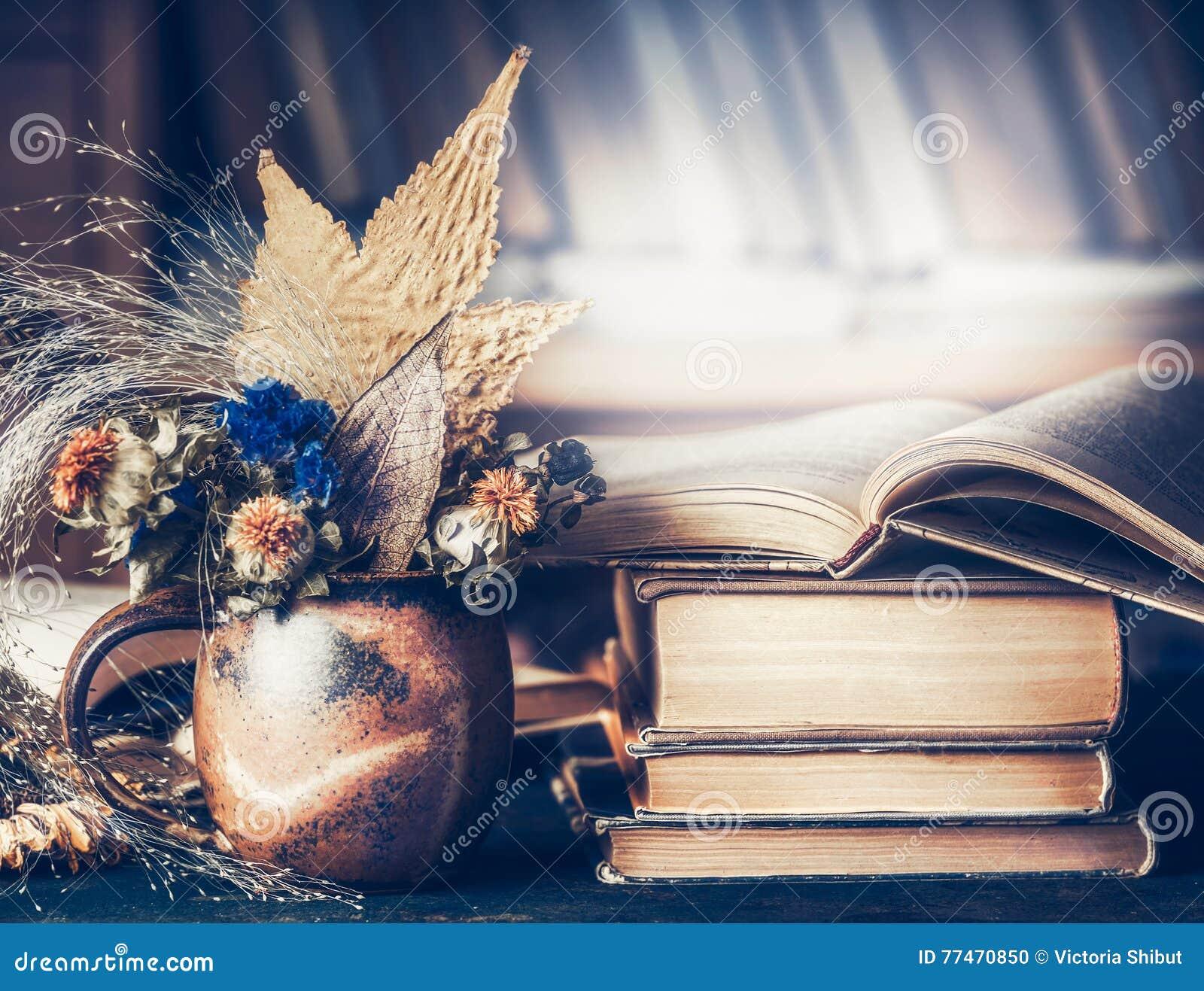 Le paysage à la maison confortable avec le bouquet d automne avec des feuilles et la chute fleurit dans la tasse avec la pile de