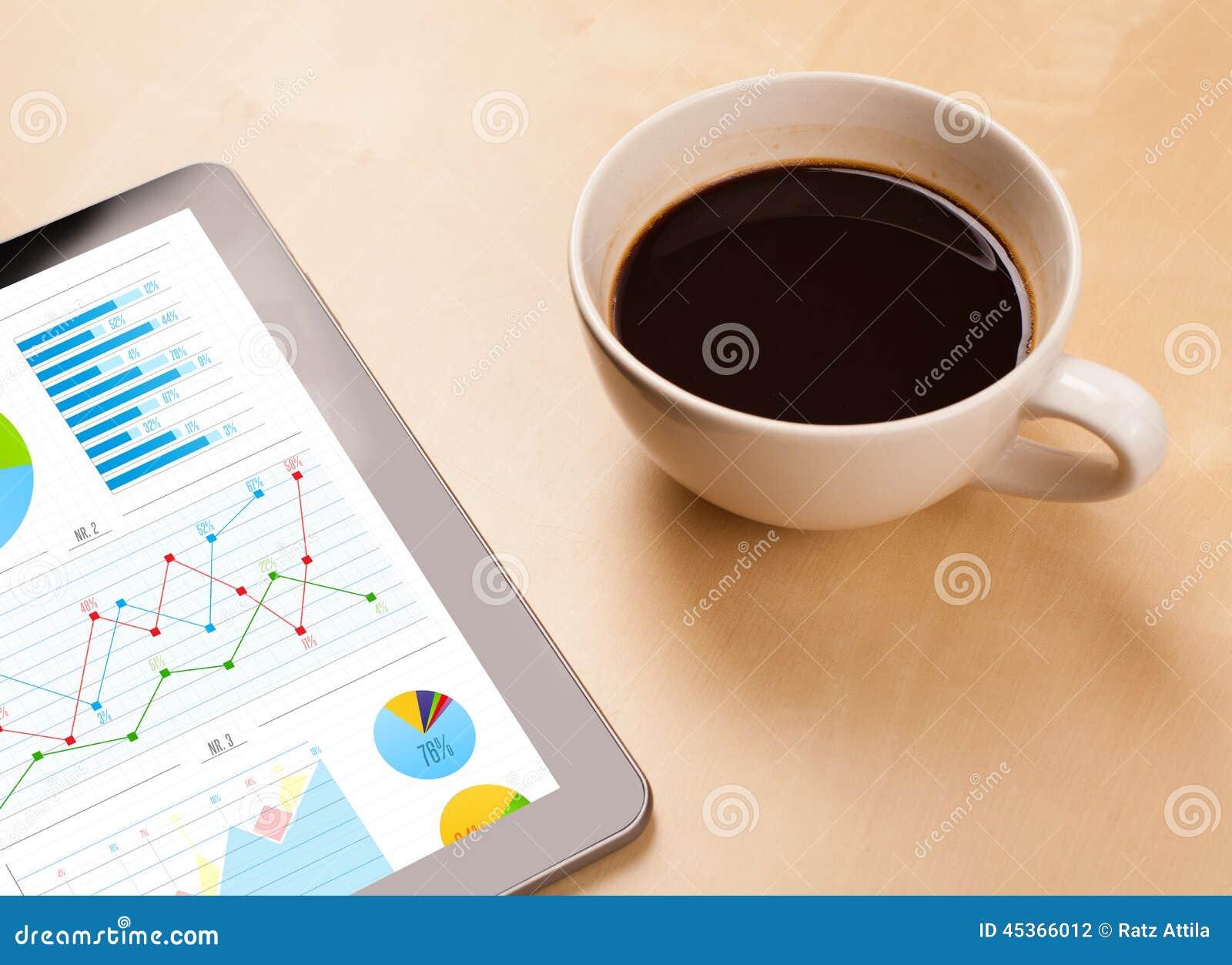 Le PC de comprimé montre des diagrammes sur l écran avec une tasse de café sur un bureau