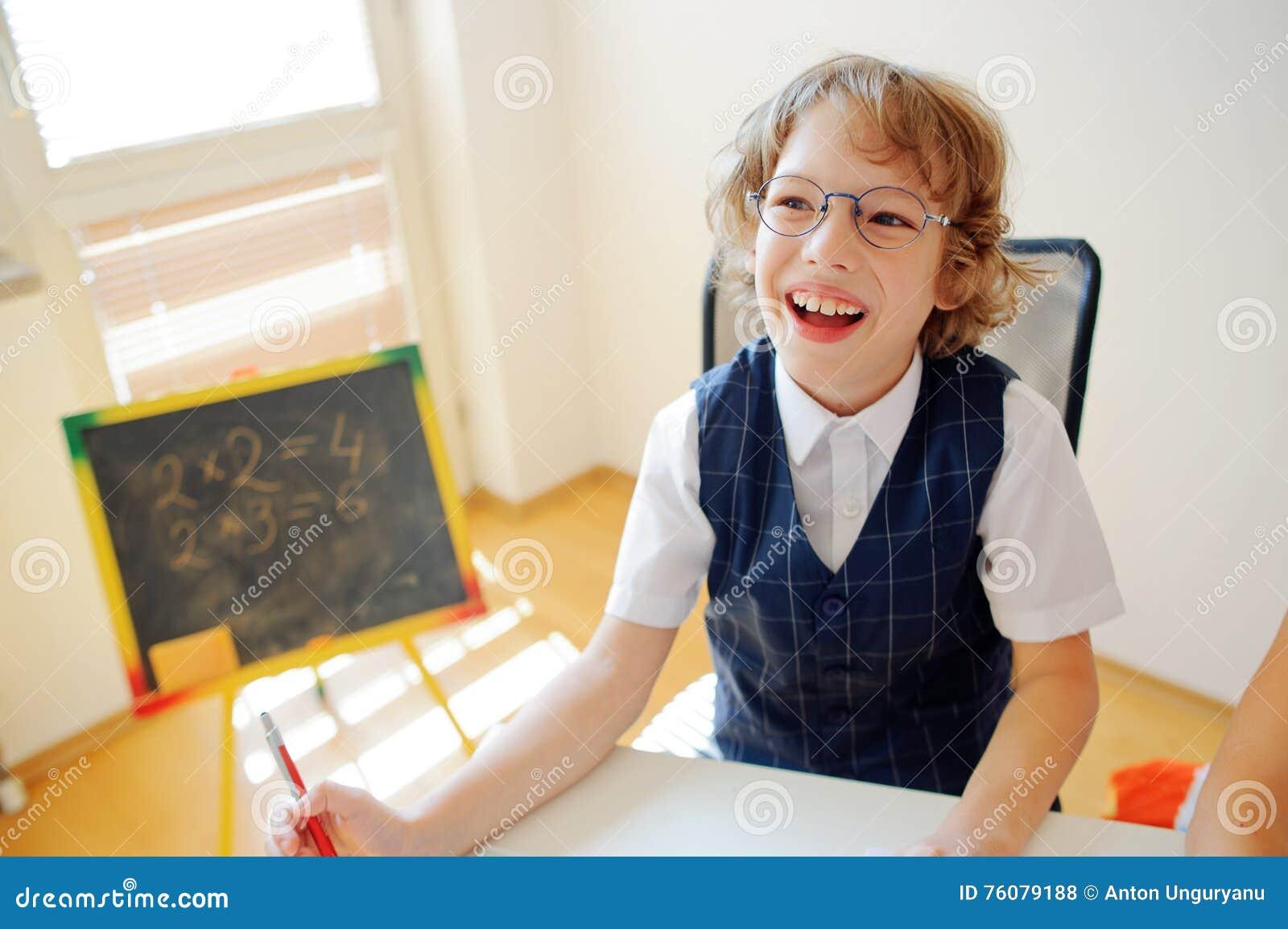 Le petit étudiant gai à lunettes s assied au bureau d école