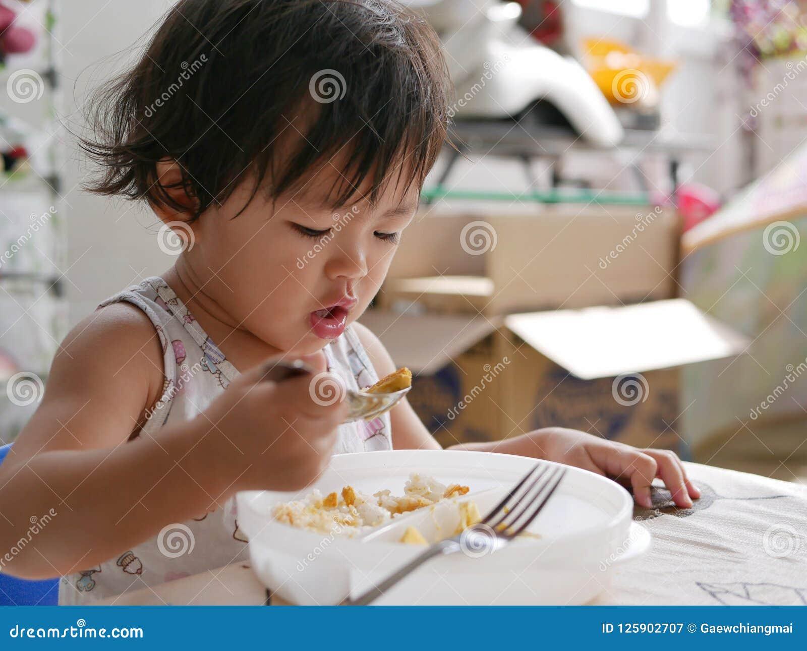 Le petit bébé asiatique a plaisir à manger de la nourriture seule
