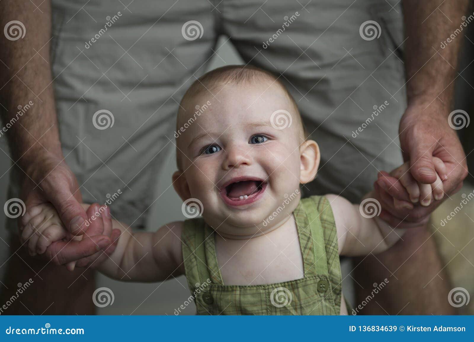 Le petit bébé garçon le plus heureux apprenant à marcher