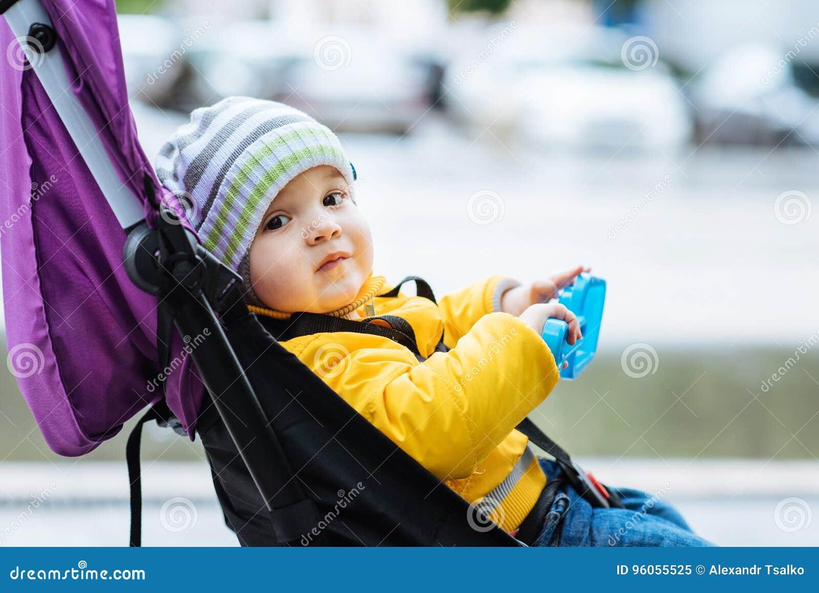 Le petit bébé s assied dans une poussette