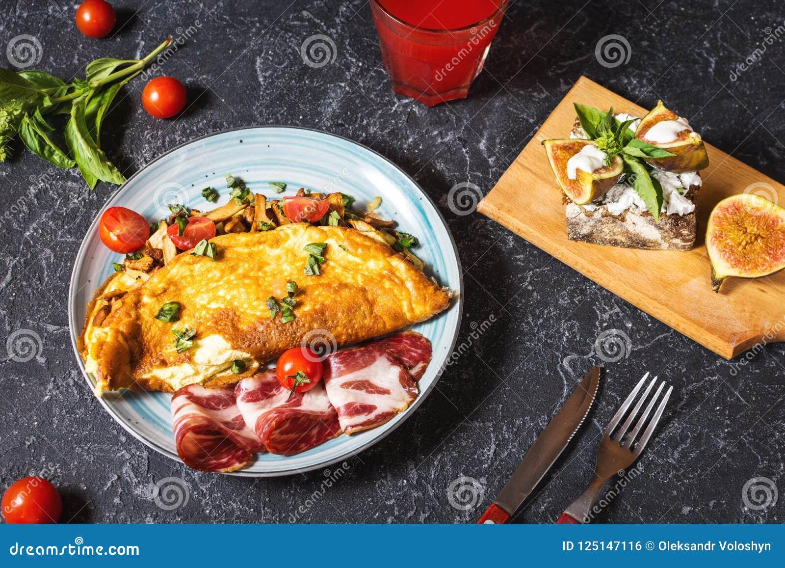 Le petit déjeuner répand omelette et sandwich avec des figues sur le fond en pierre