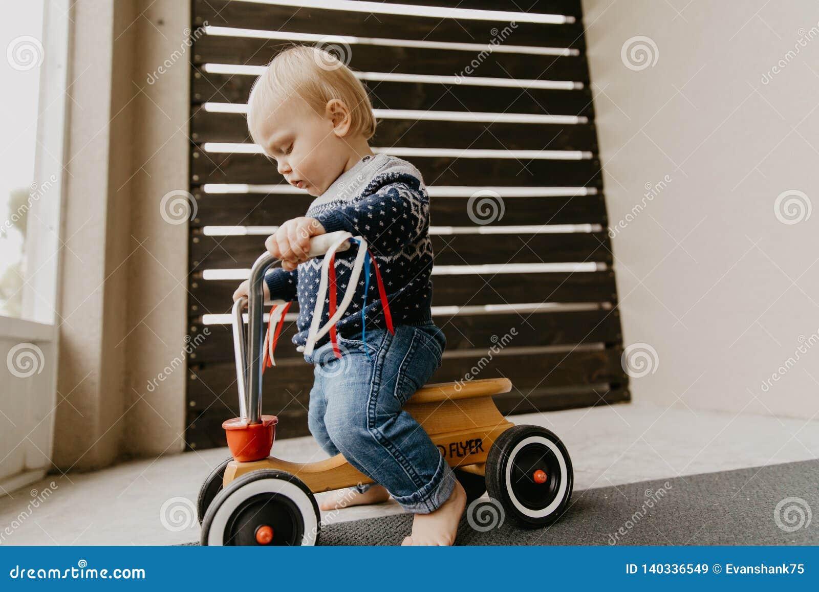 Le petit enfant blond mignon adorable précieux de garçon d enfant en bas âge de bébé jouant dehors sur Toy Bicycle Scooter Mobile